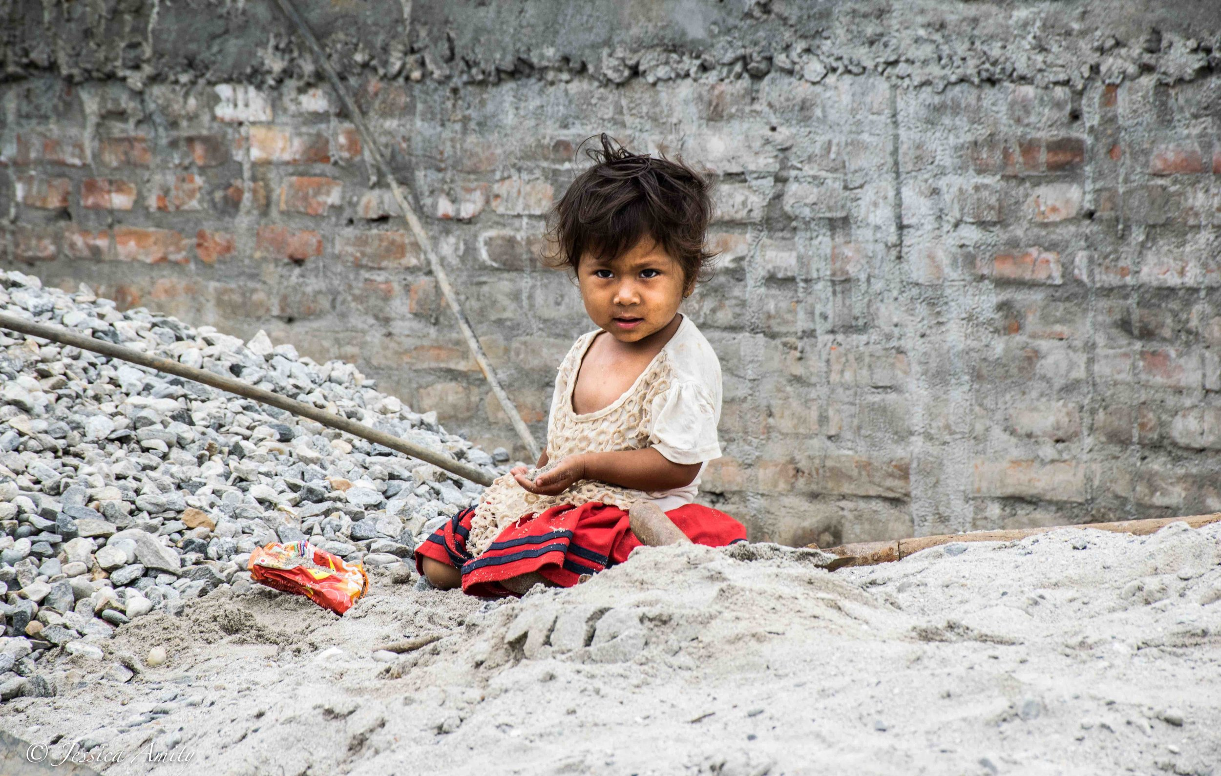 A little girl plays in the rubble during the construction of a new home in Sindupolchok, Nepal. In Nepal, 25.2% of the population live below the national poverty line.