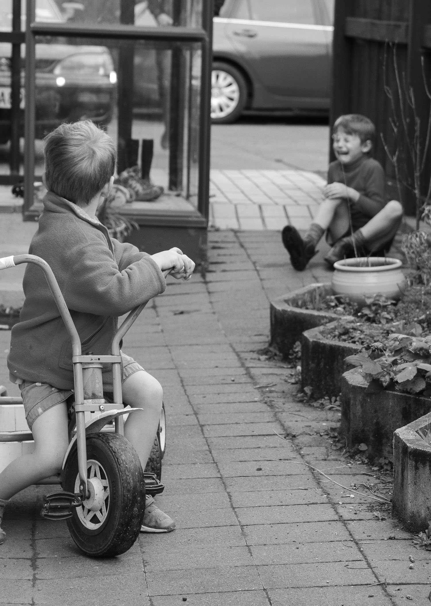 brothers-playing-together-on-trike-outside-family-home-black-and-white-one-boy-fallen-off-trike.jpg
