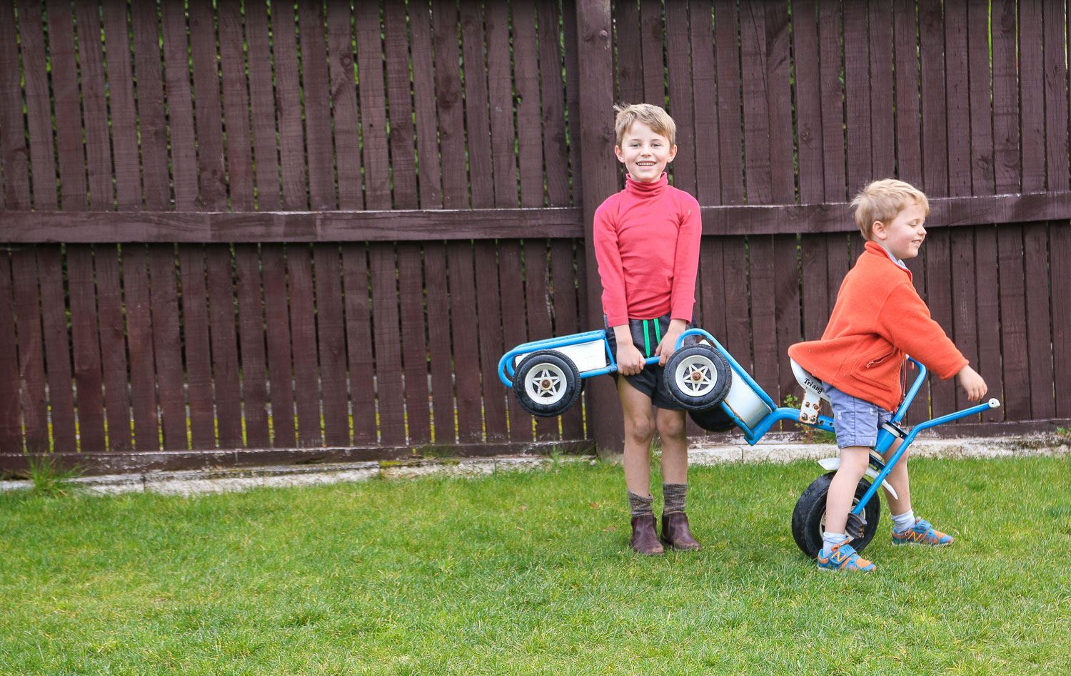 brothers-playing-together-with-trike-in-garden.jpg