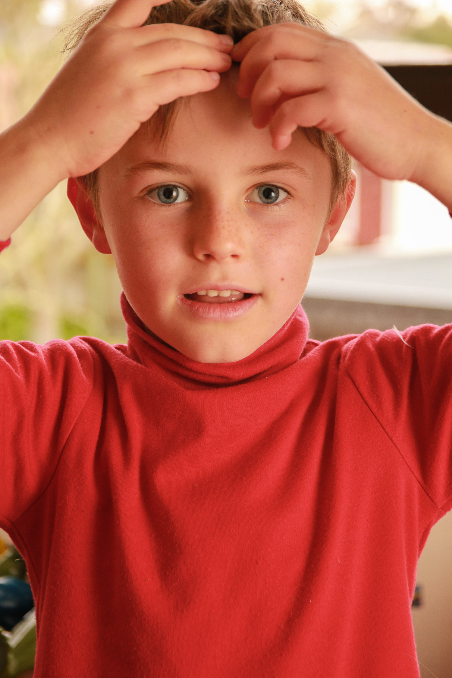 boy-wearing-red-holding-his-head-blue-eyes