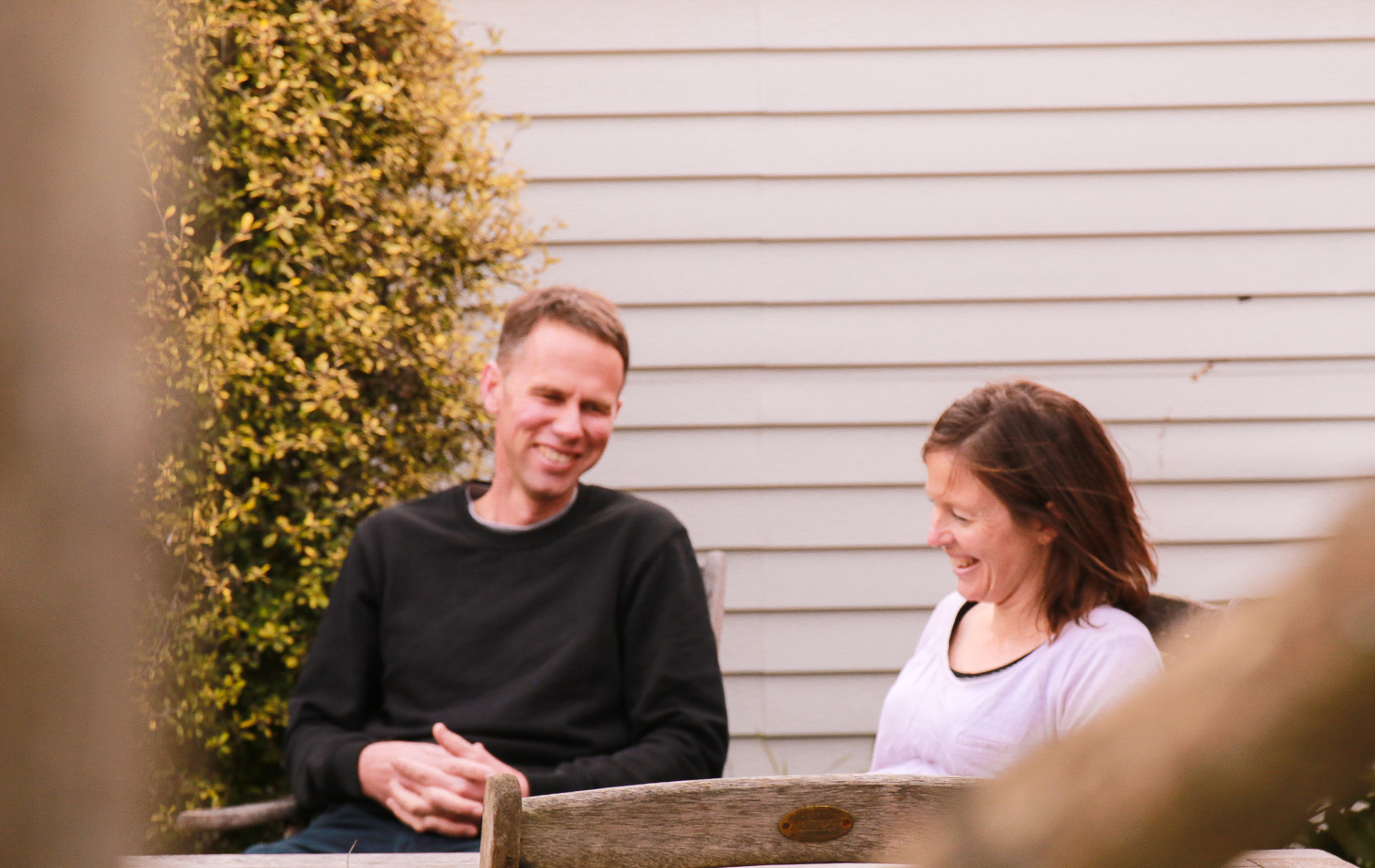husband-and-wife-laughing-together-sitting-in-their-garden.jpg
