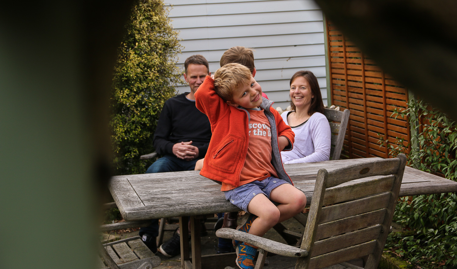 little-boy-wearing-orange-sitting-on-outside-table-pulling-funnny-face-family-in-background-laughing.jpg