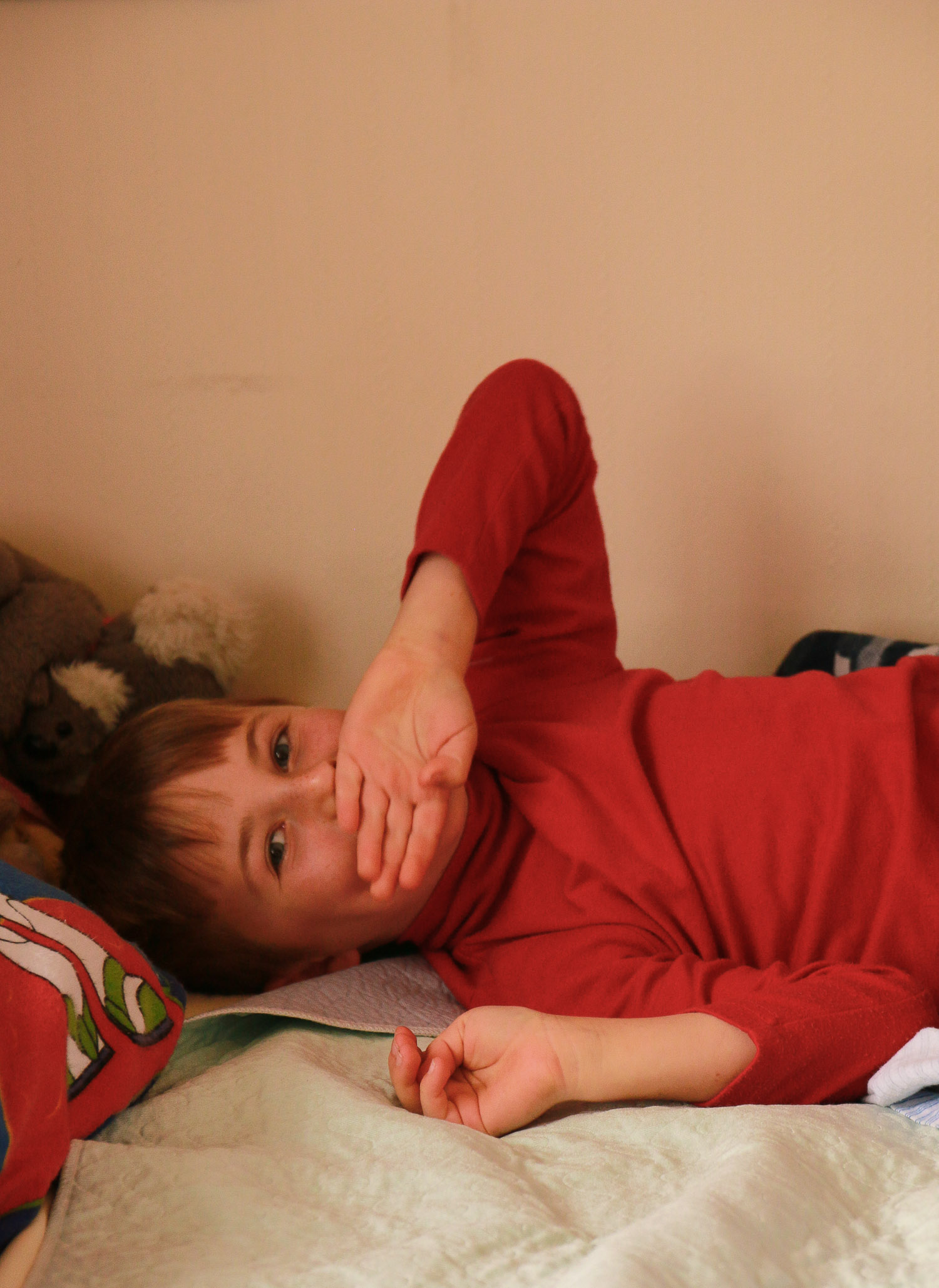 young-boy-wearing-red-lying-on-bed-looking-at-camera.jpg