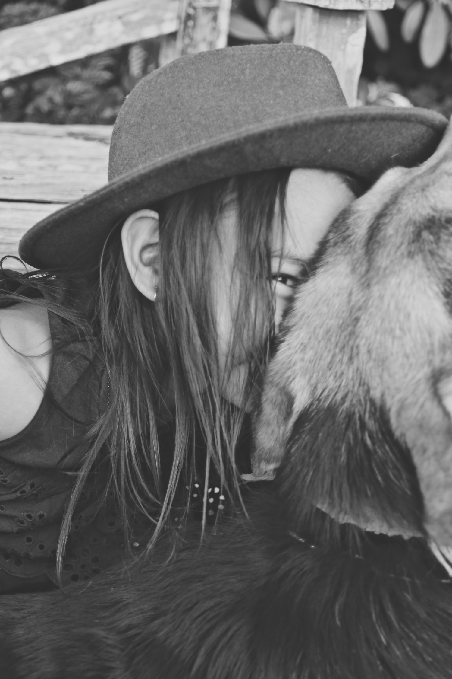 black-and-white-image-of-girl-wearing-farm-hat-cuddling-into-farm-dog_L-R.jpg