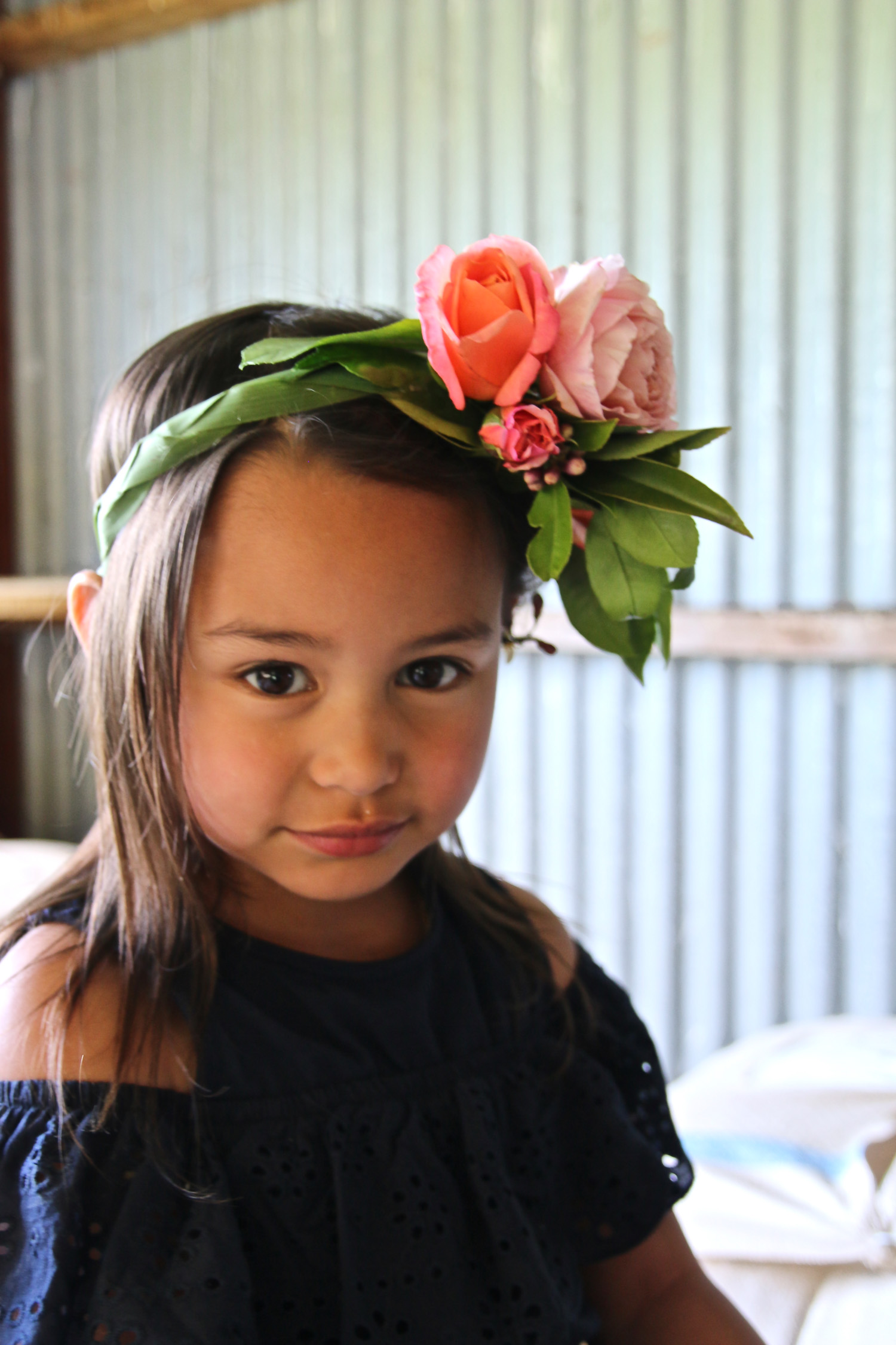 little-girl-looking-at-camera-sitting-in-woolshed-wearing-flower-crown_L-R.jpg
