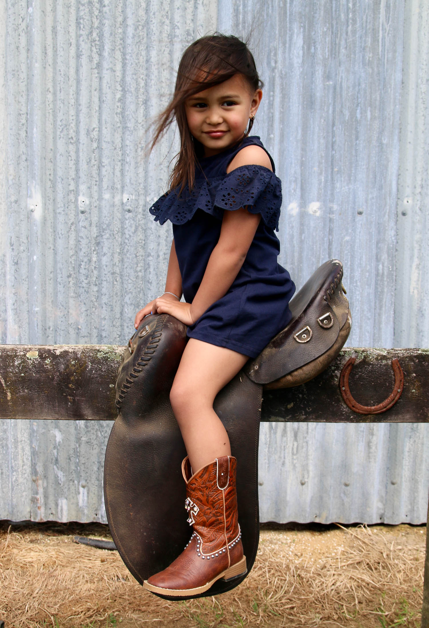 little-girl-sitting-on-stock-saddle-wearing-cowboy-boots_L-R.jpg