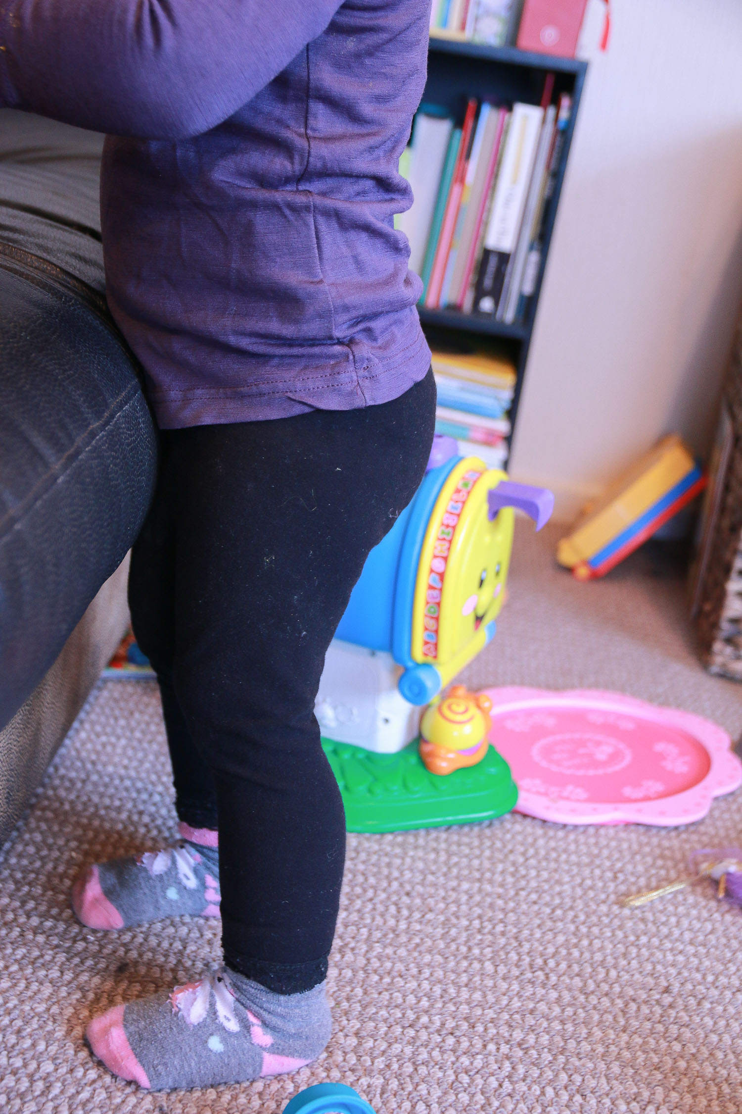 little-girl-standing-by-couch-toys-all-around-her-purple-top-and-cute-tights.jpg