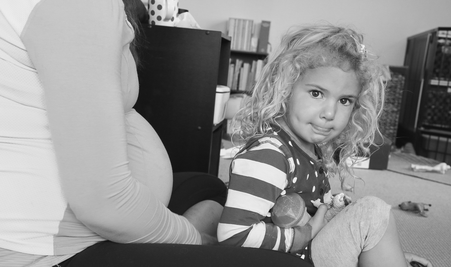 little-girl-sitting-with-pregnant-mum-looking-at-camera-black-and-white
