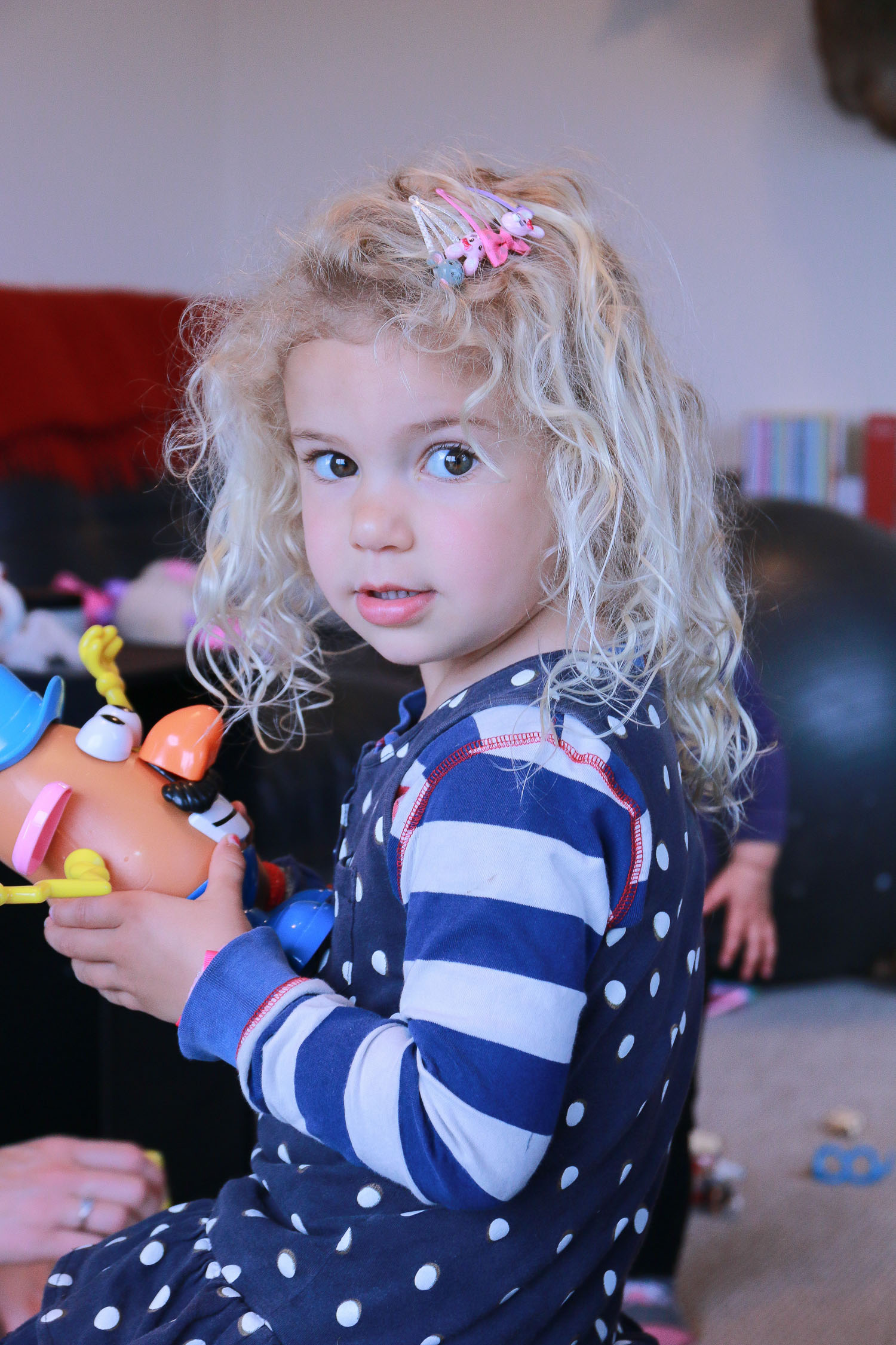 little-girl-playing-in-lounge-clips-in-hair-with-mr-potato-head