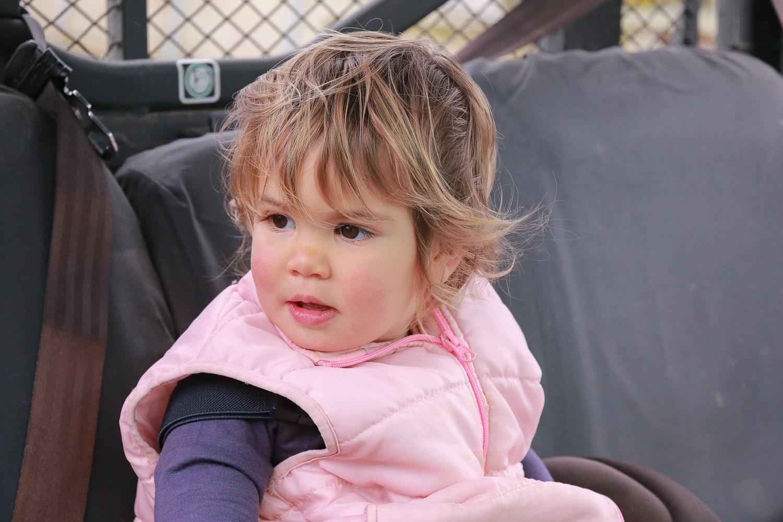 little-girl-sitting-in-side-by-side-wearing-pink-red-cheeks