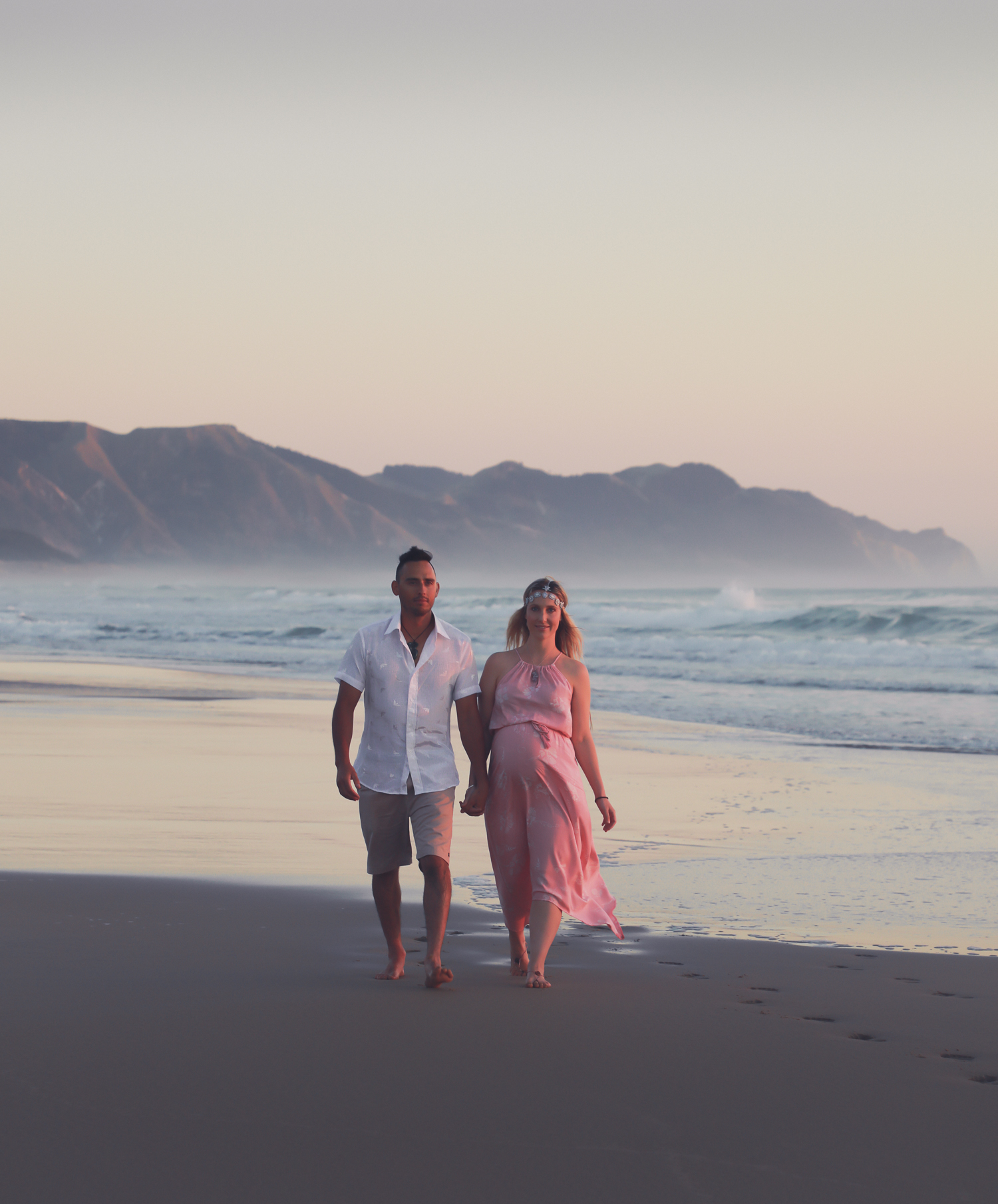 pregnant woman at beach at sunrise with husband walking along beach
