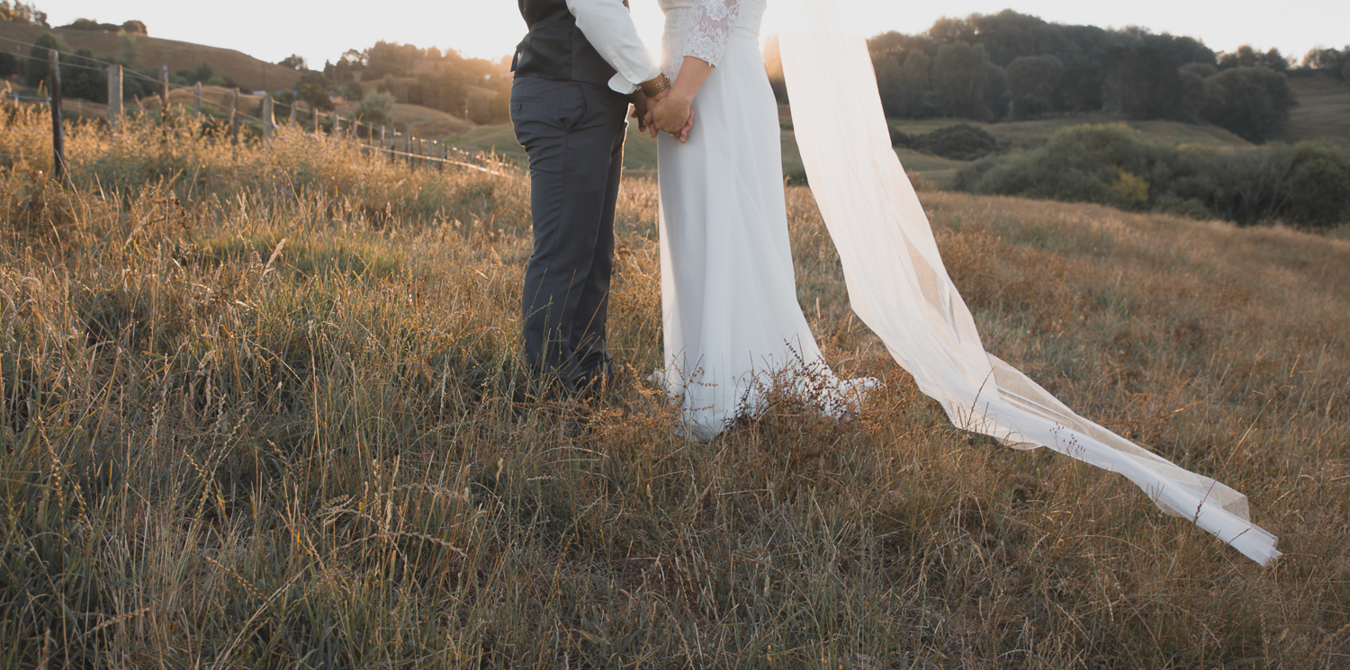 bride and groom walking on wedding day in long grass