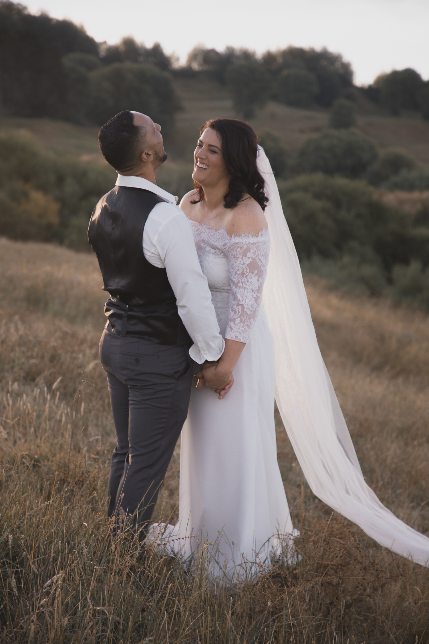 bride and groom laughing together on farm at sunset