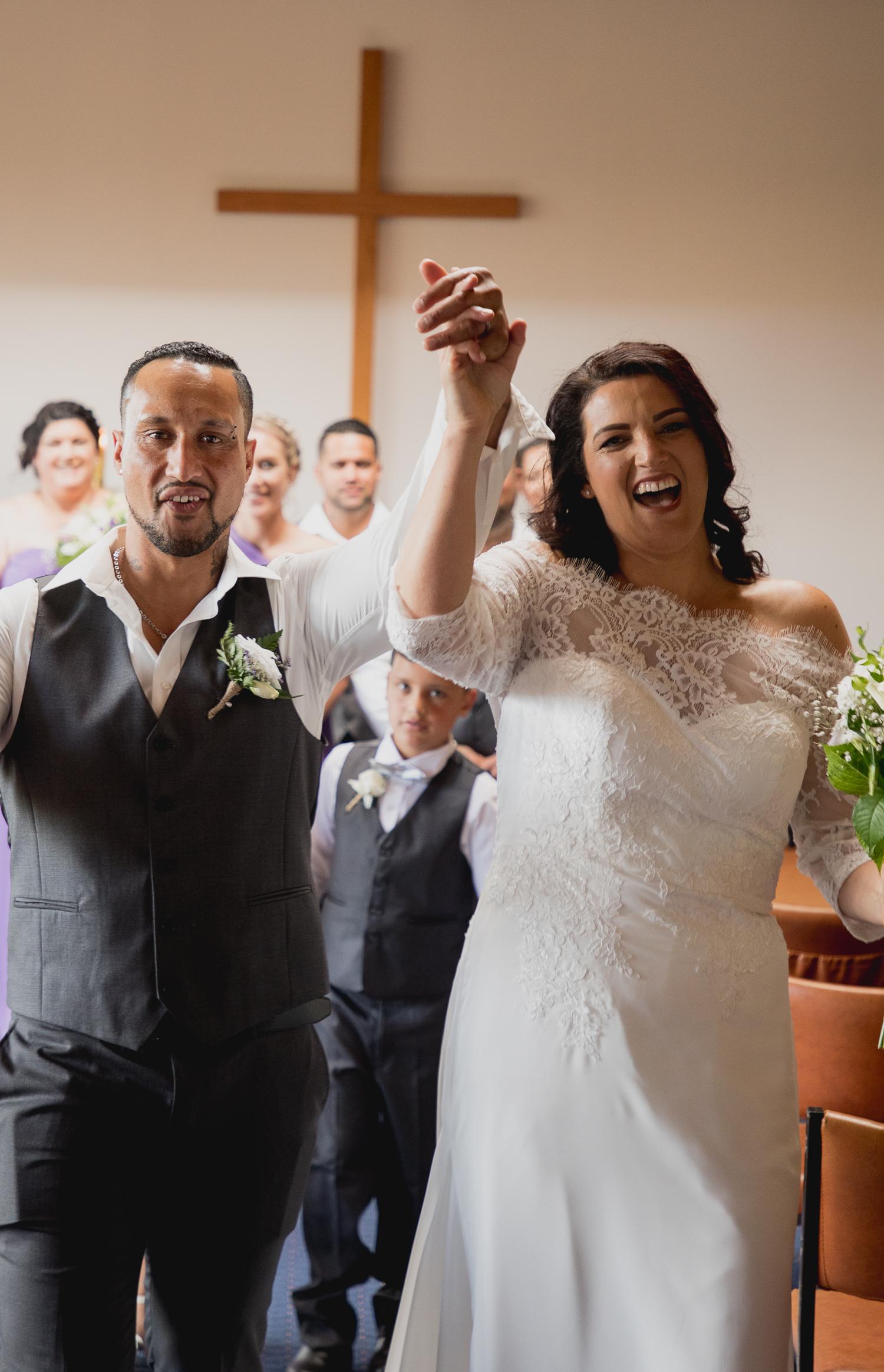 husband and wife walking down isle celebrating getting married