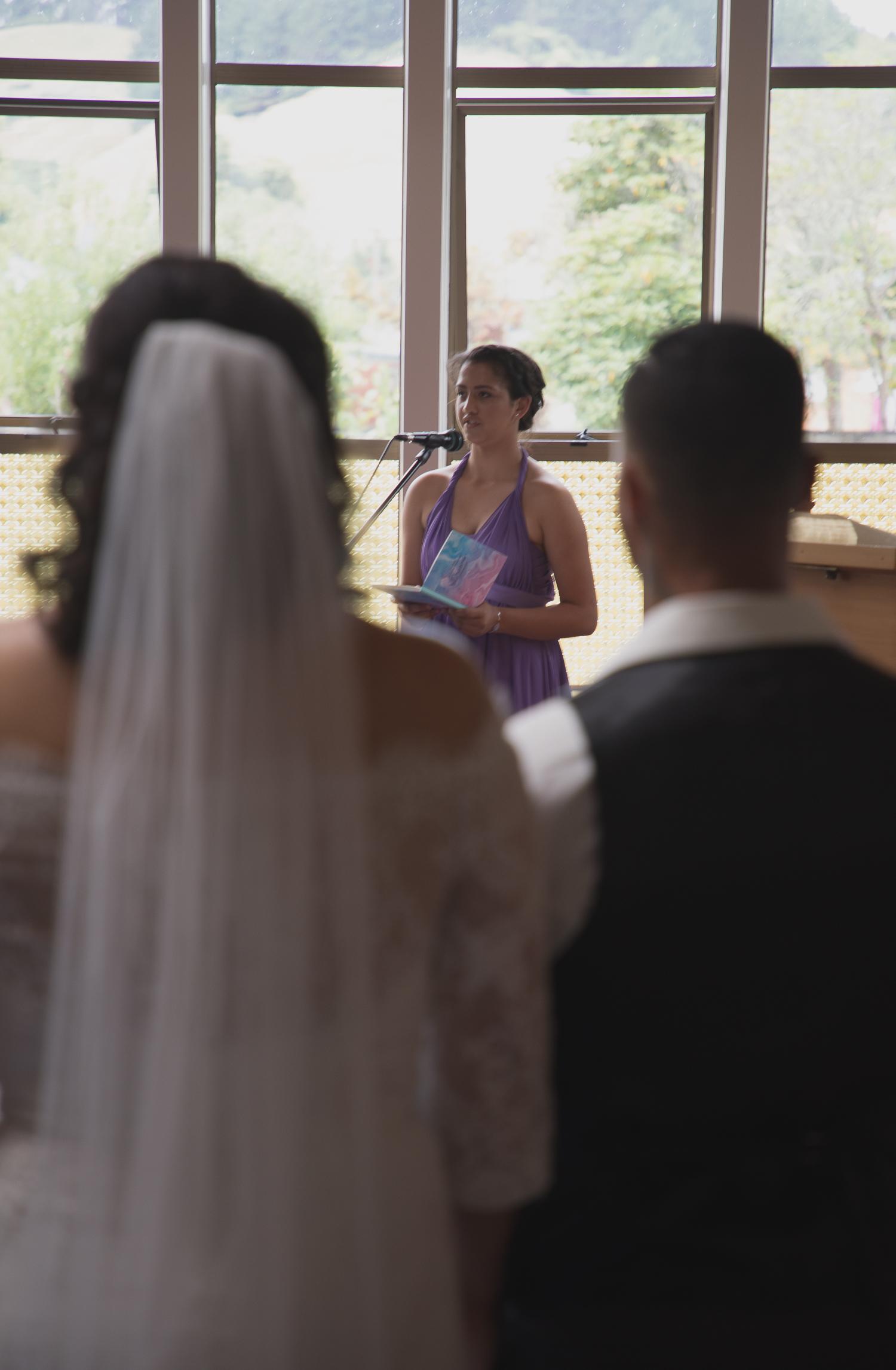 bridesmaid singing as bride and groom watch on