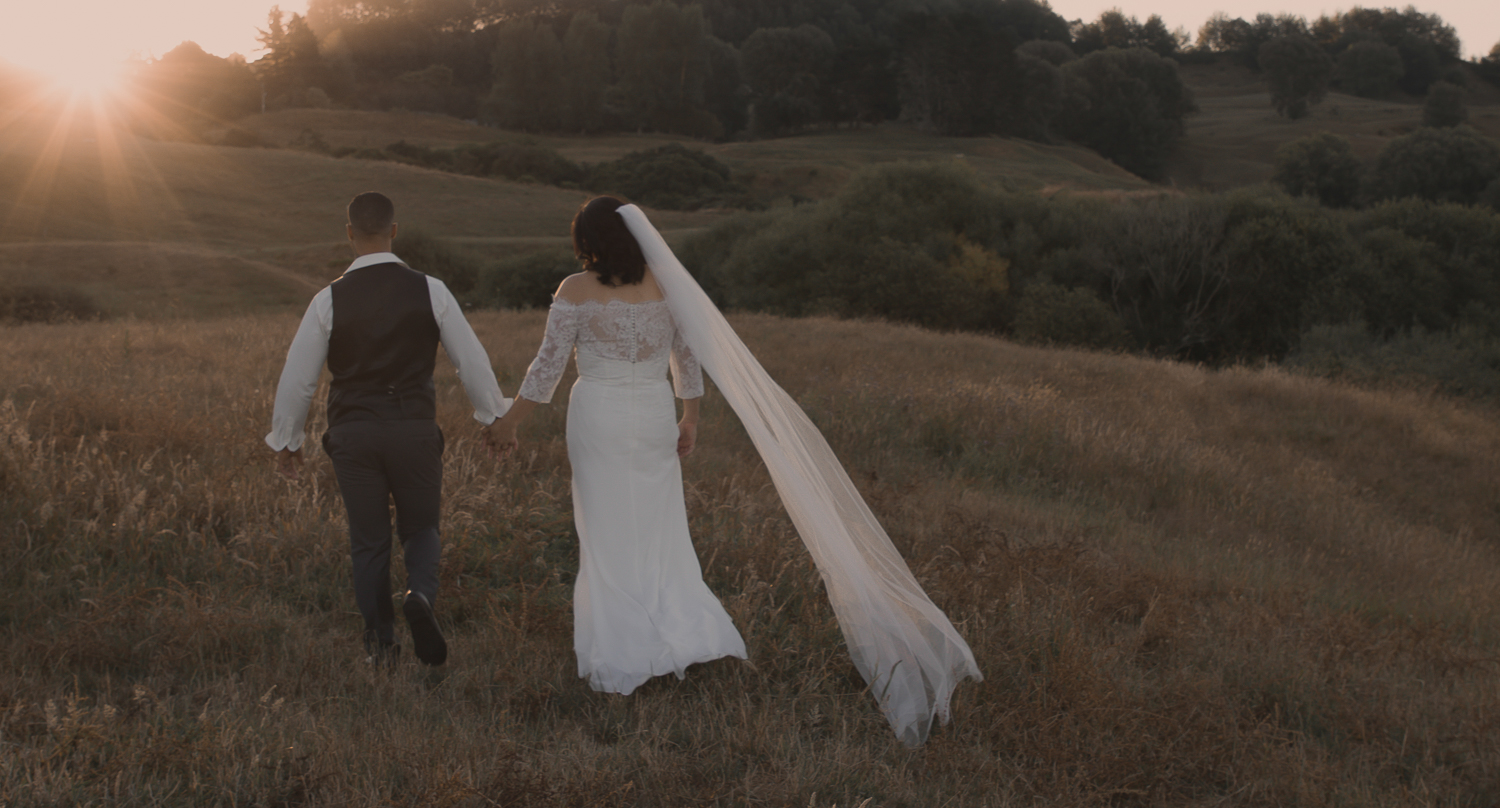 bride and groom walking into sunset on wedding day in long grass