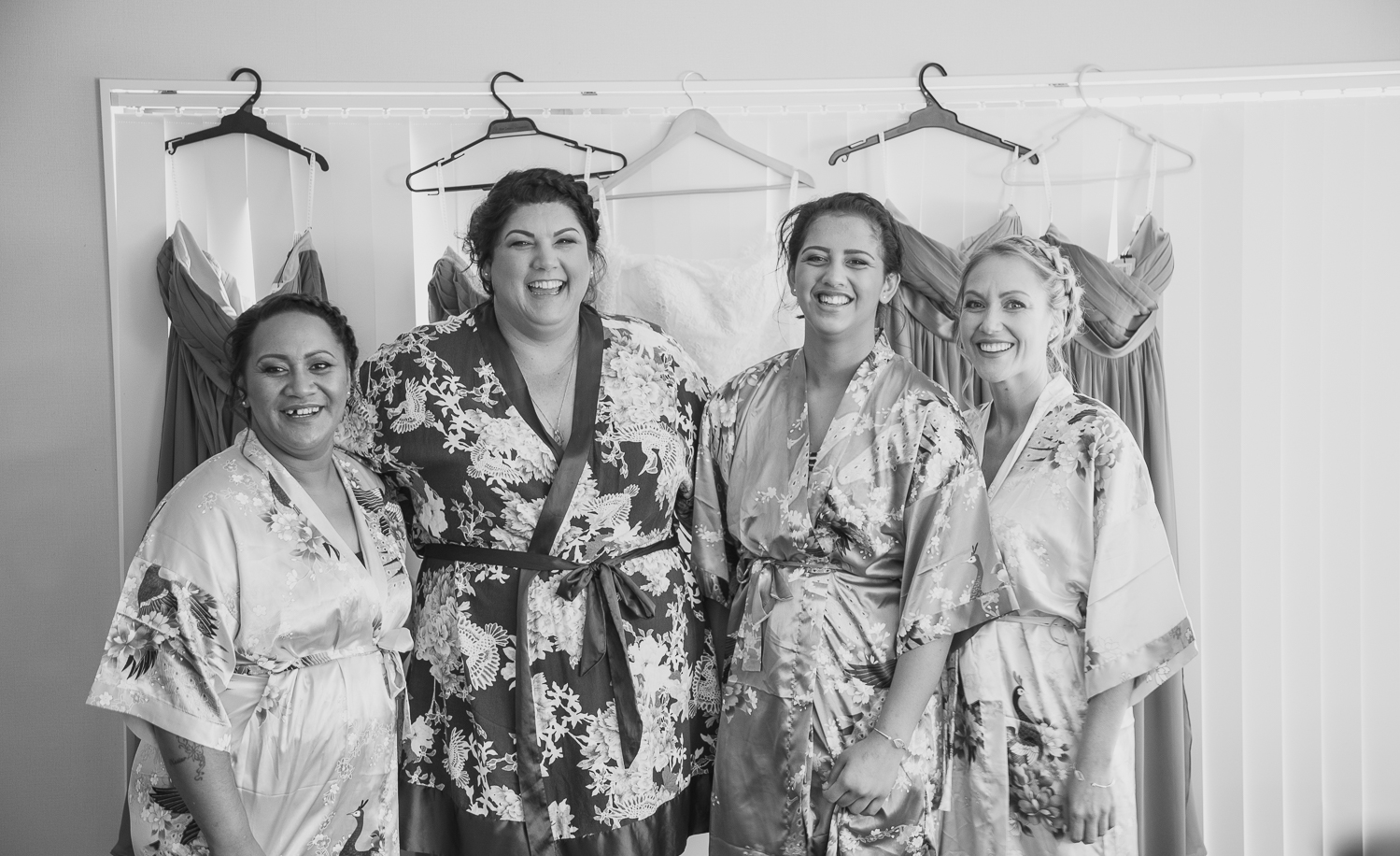 bridesmaids in front of wedding dresses