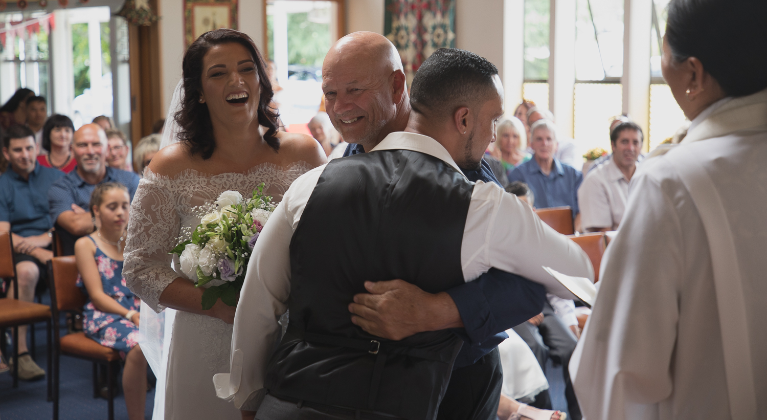 father of the bride and groom hugging at alter