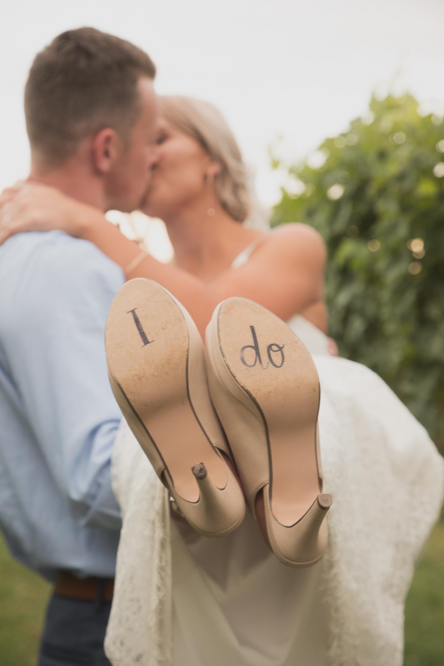 groom lifitng bride up shoes saying i do