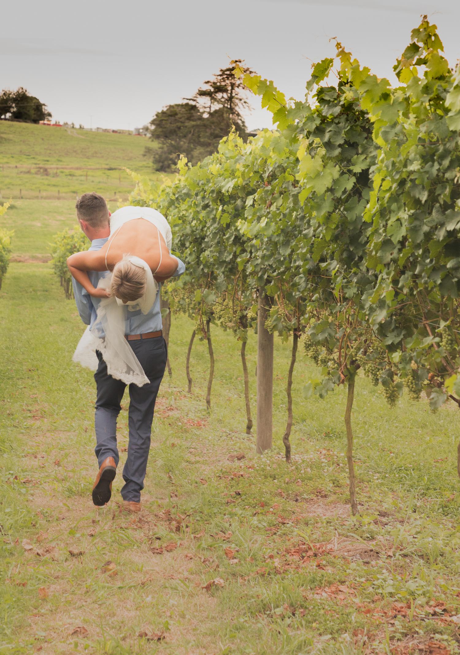 groom carrying bride on wedding day