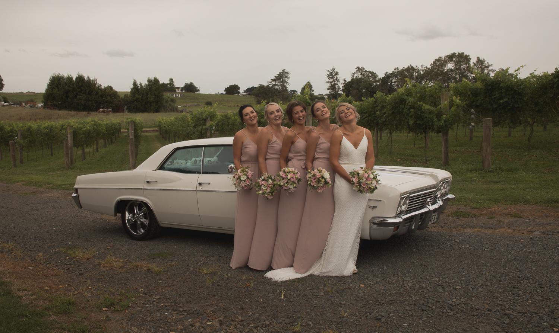 bride and bridesmaid with wedding car