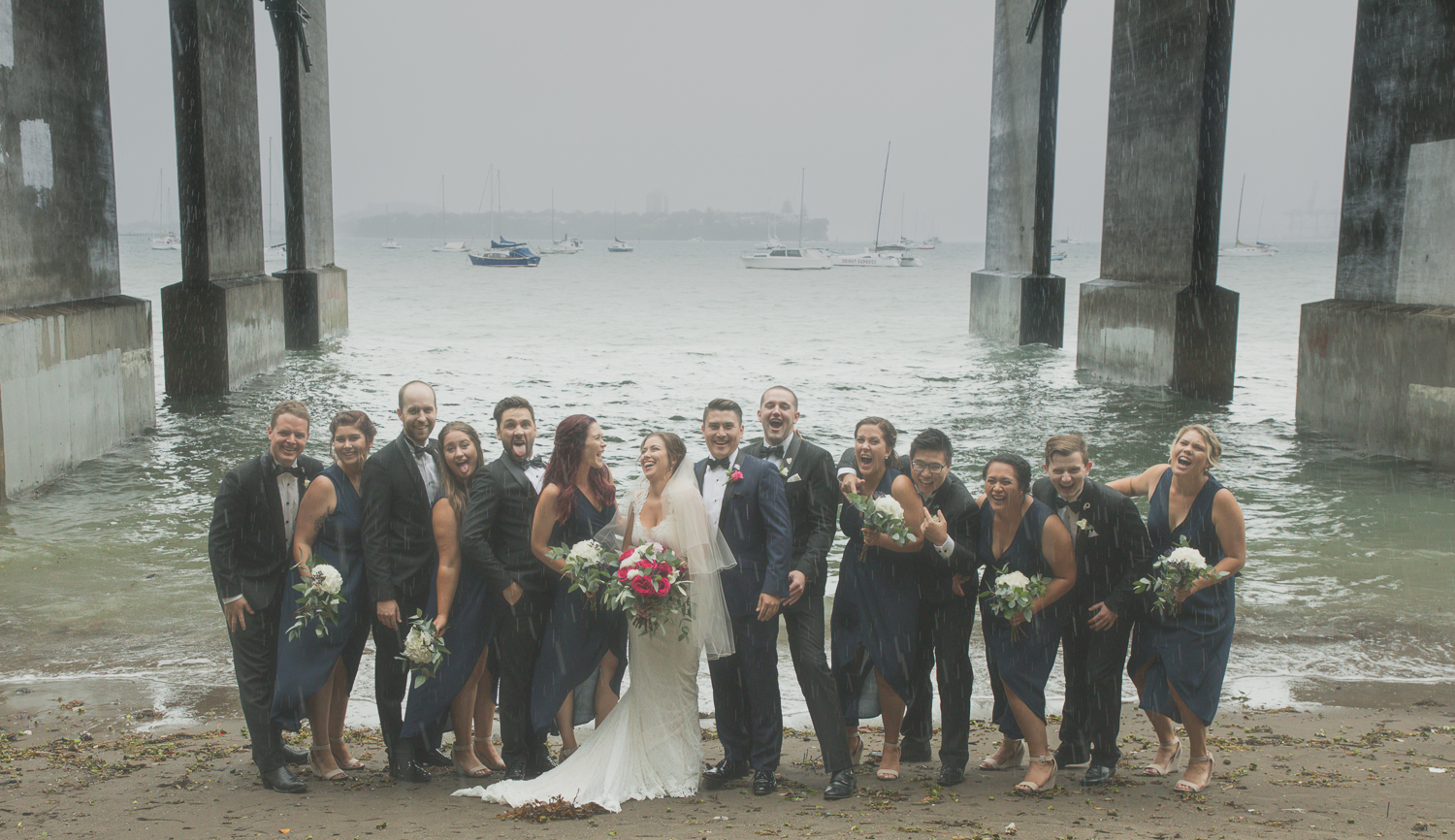bridal party having photos in the rain