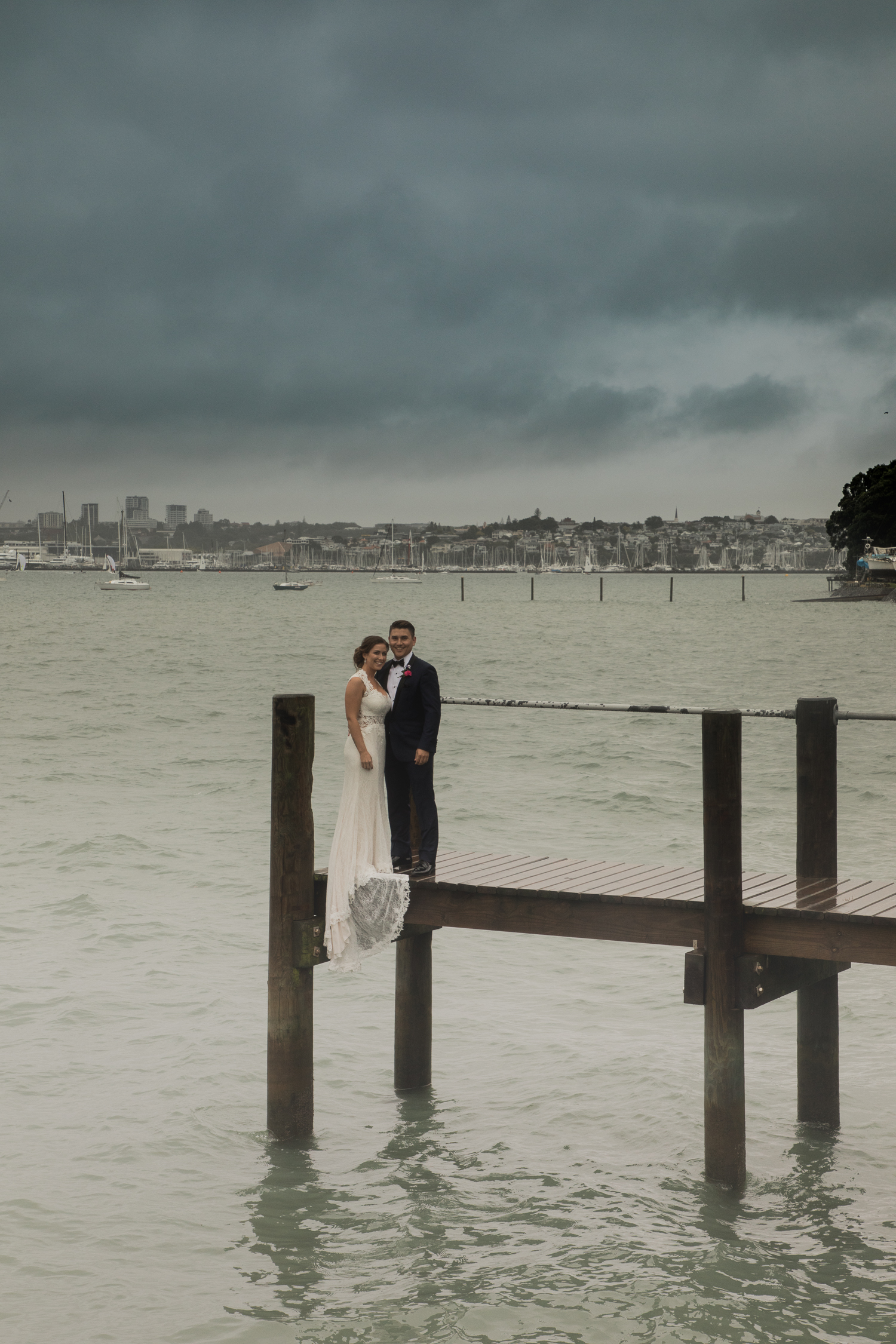 bride and groom on wharf overlooking Auckland city