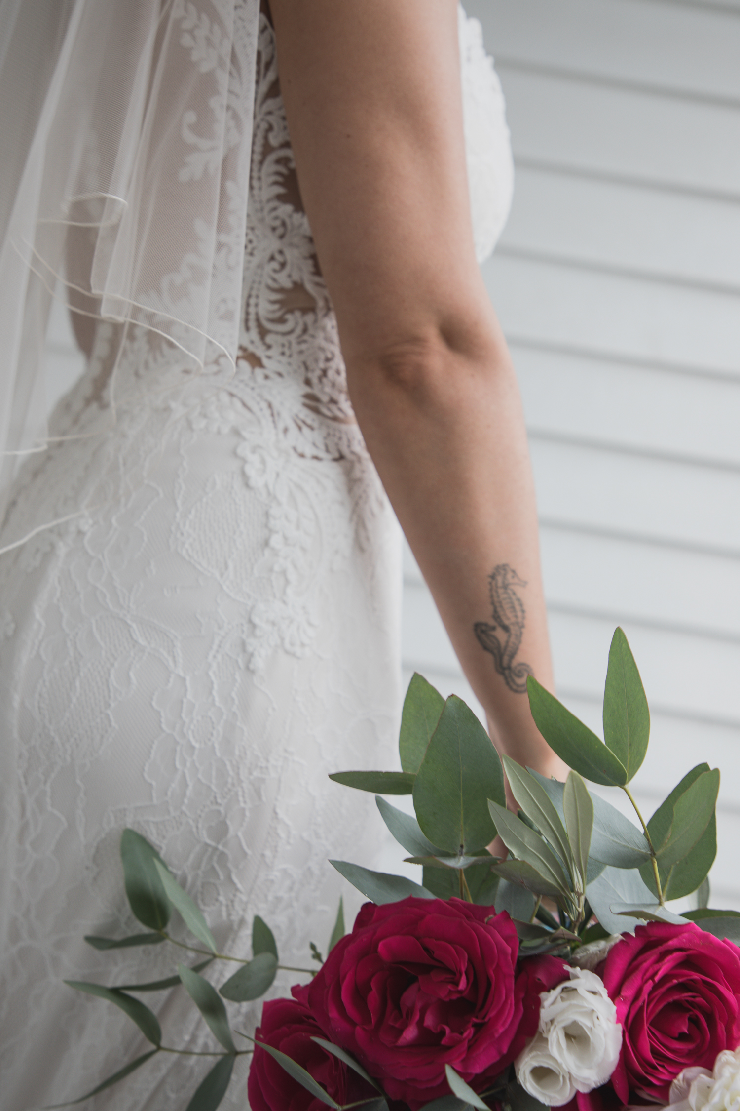 bride-standing-outside-house-with-amazing-detail-on-dress-and-florals-with-seahorse-tattoo.jpg