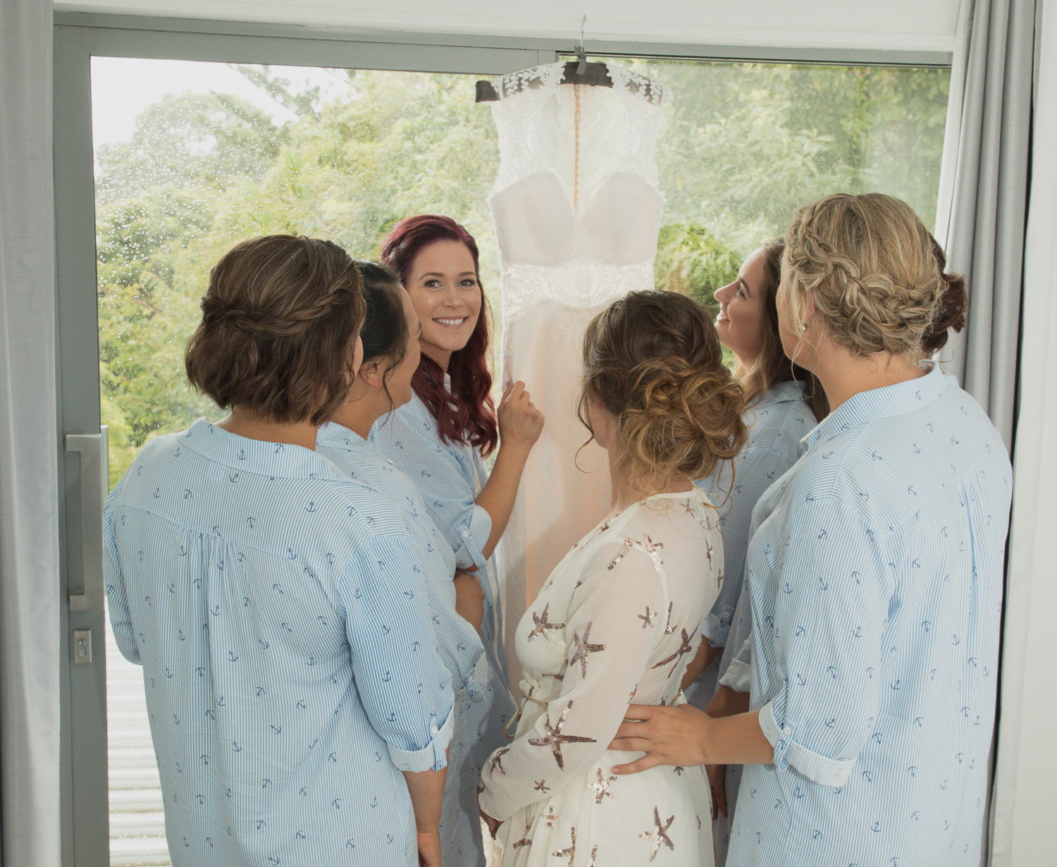 bride with bridesmaids looking at wedding dress