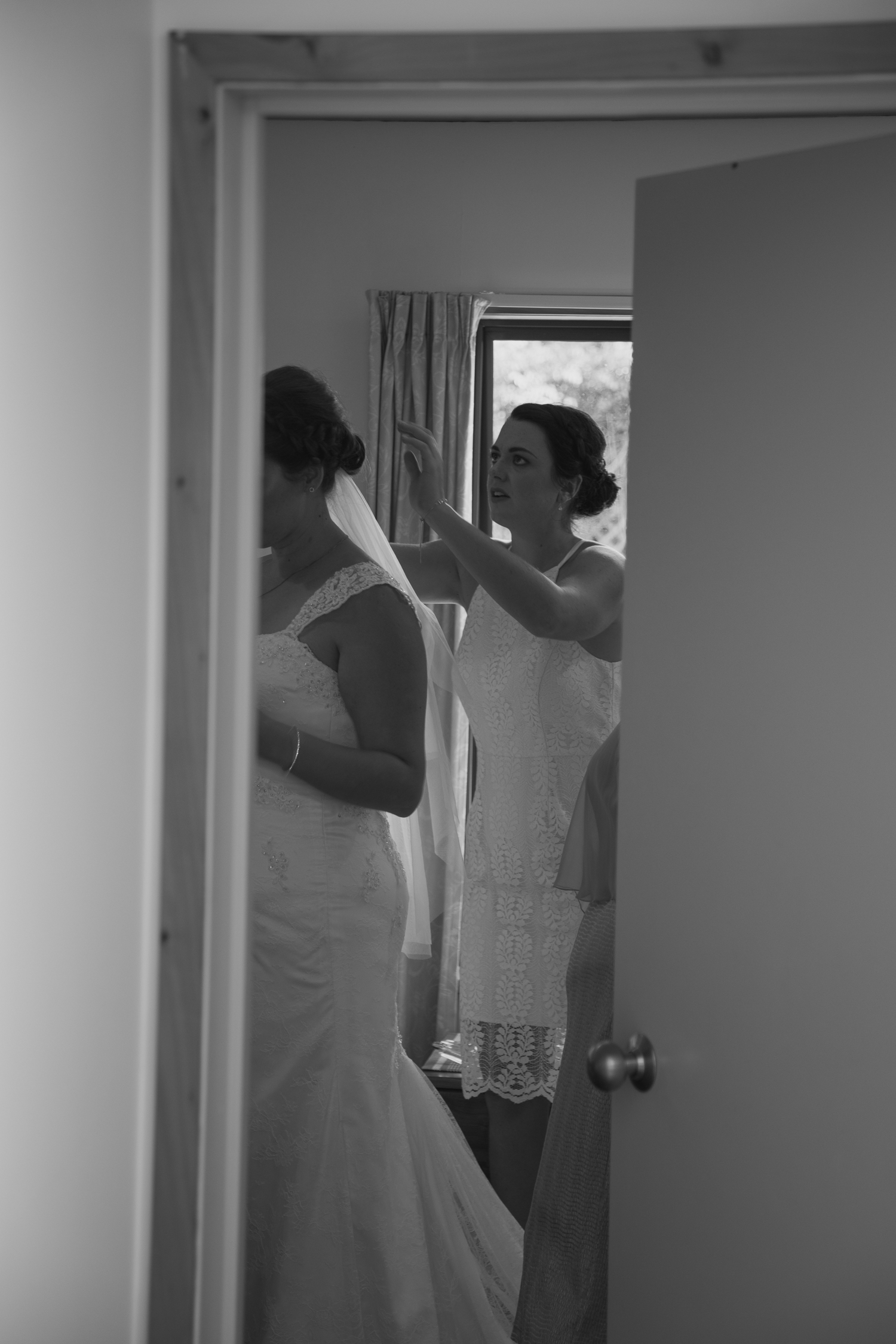 maid of honour helping bride with veil on wedding day