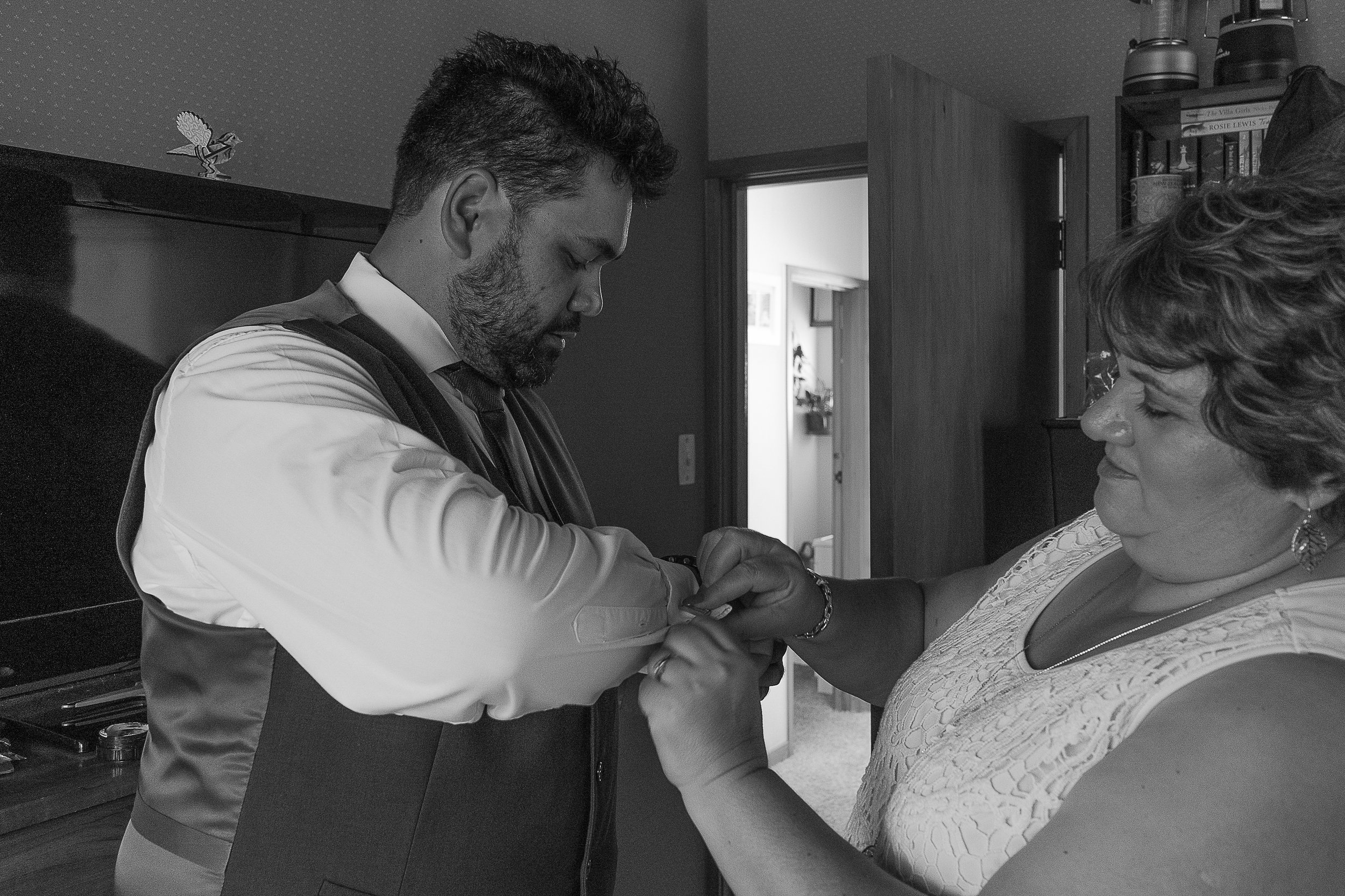 grooms mother helping him do up shirt on wedding day