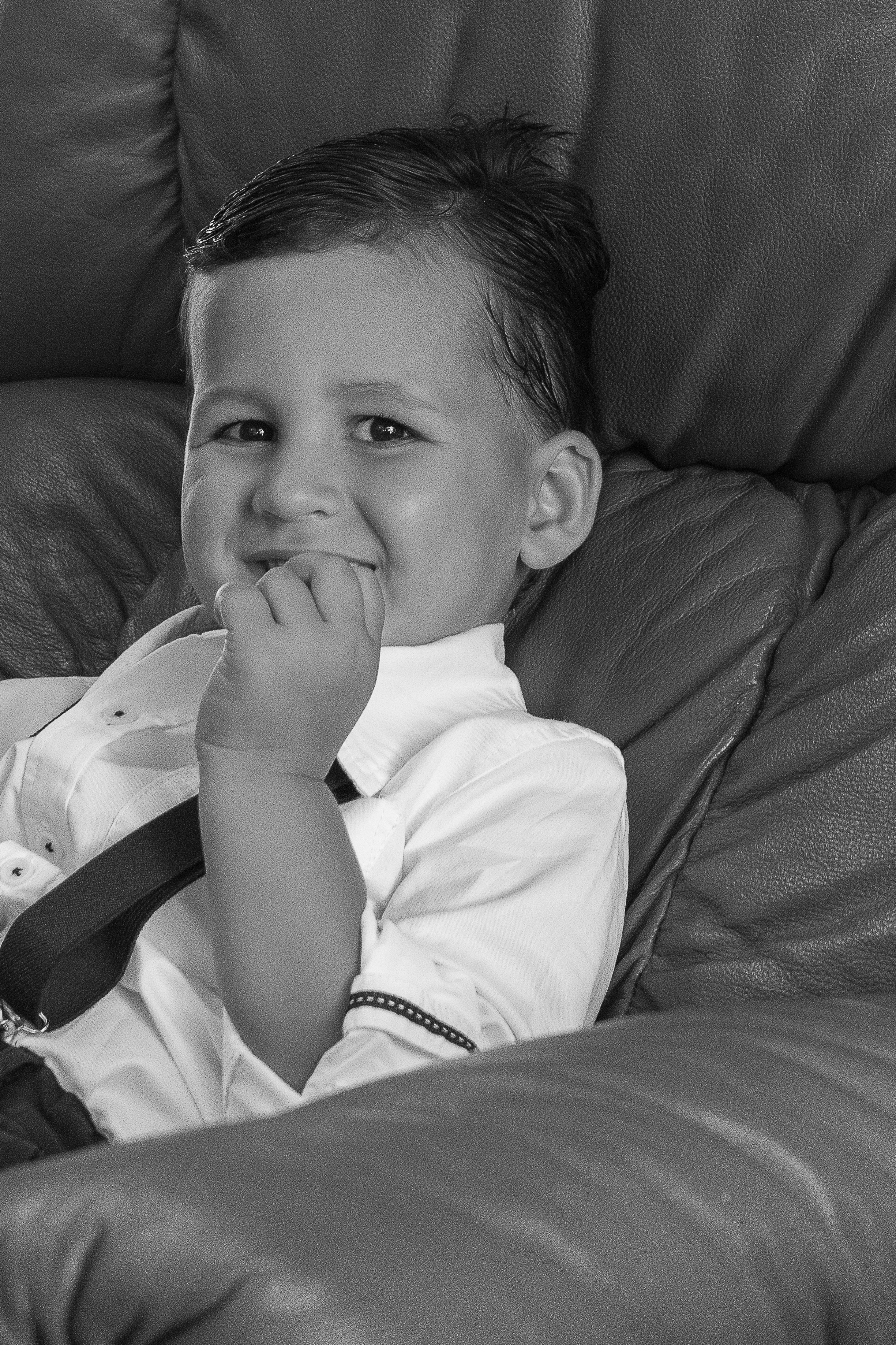 little boy sitting on the couch in suit