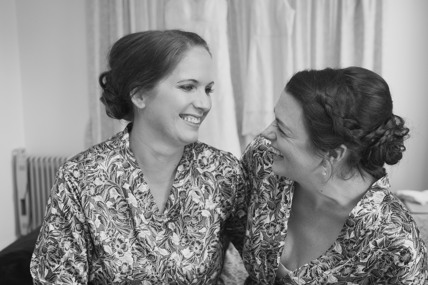 bride and maid of honour laughing together with wedding dresses in background