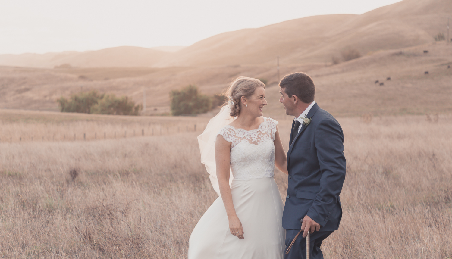 bride-and-groom-standing-together-on-their-farm-at-sunset.jpg