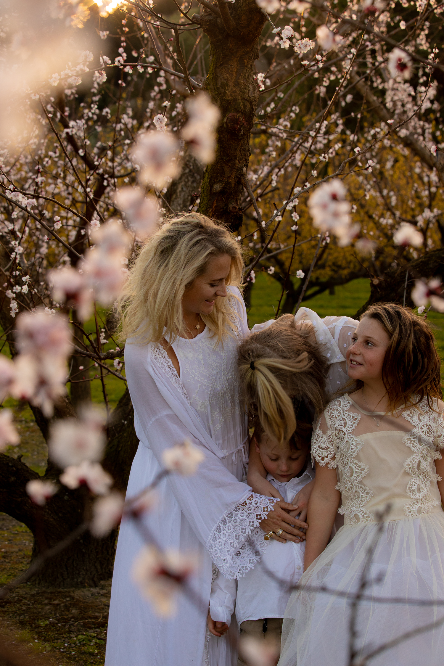 Hawkes-bay-photographer-at-sunset-in-orchard-in-the-blossoms-laughing-together-mother-with-her-children.jpg