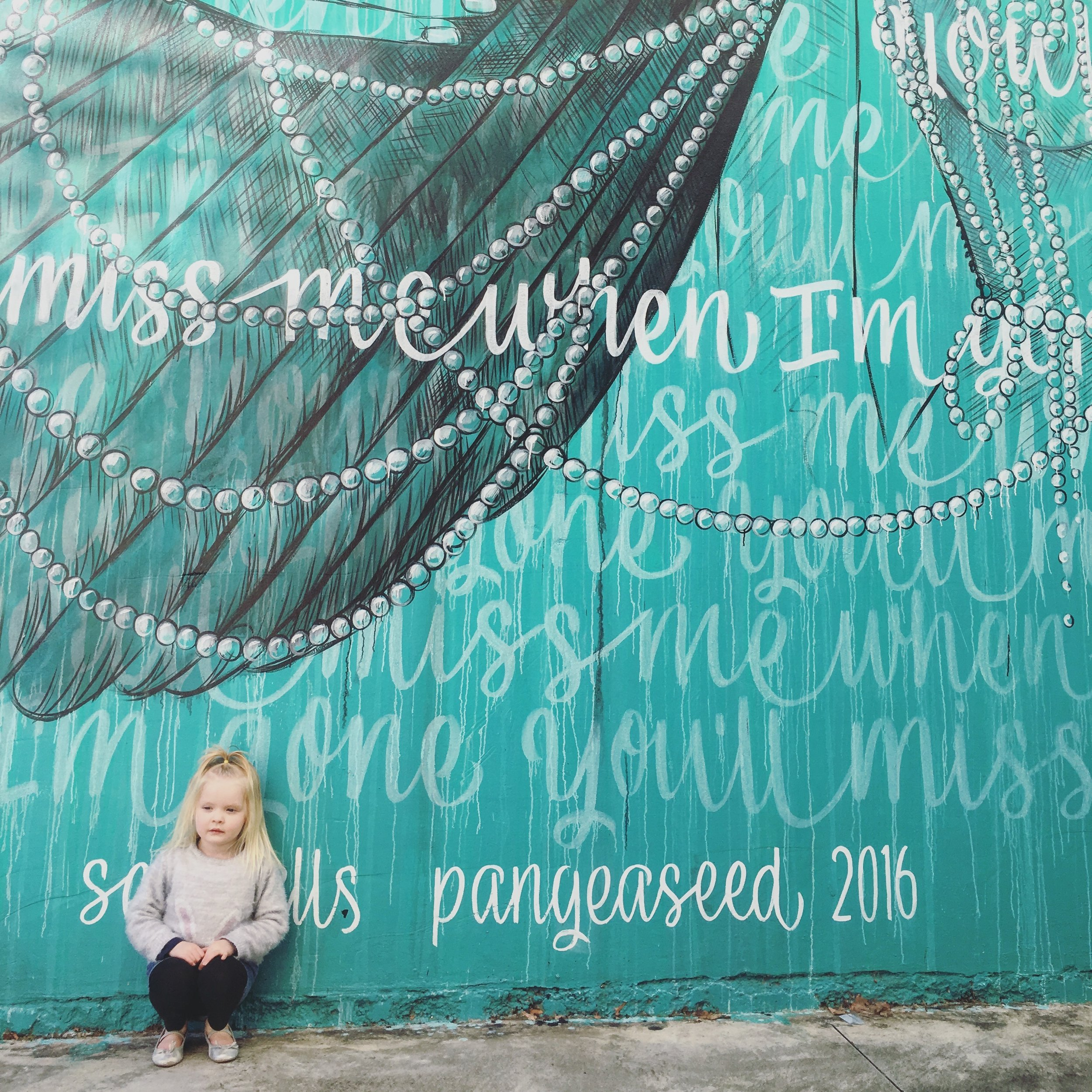 new-zealand-napier-sea-wall-with-little-blonde-girl-sitting-beside-it.jpg