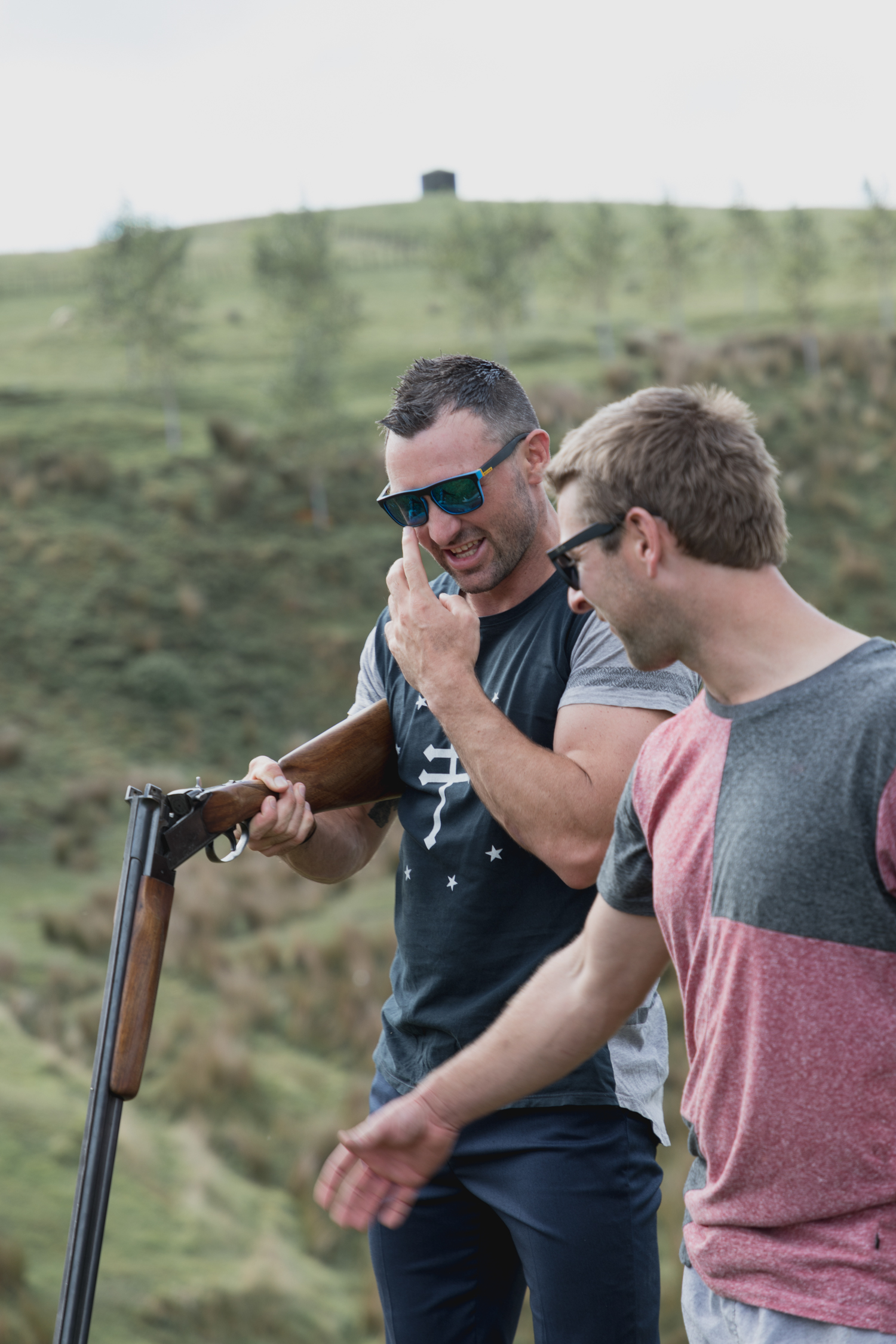 wedding-at-the-red-barn-new-zealand-wedding-photographer-groom-and-groomsmen-shooting-clays-laughing.jpg