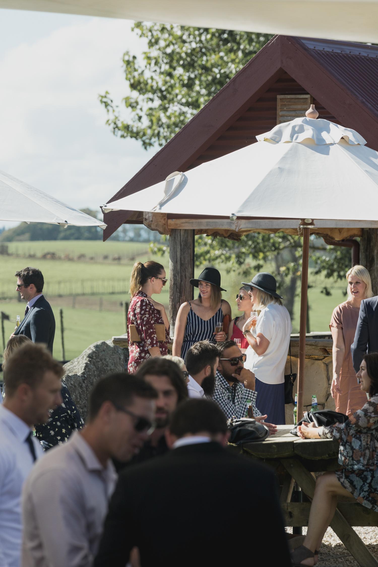 wedding-at-the-red-barn-new-zealand-wedding-photographer-guests-under-umbrellas.jpg