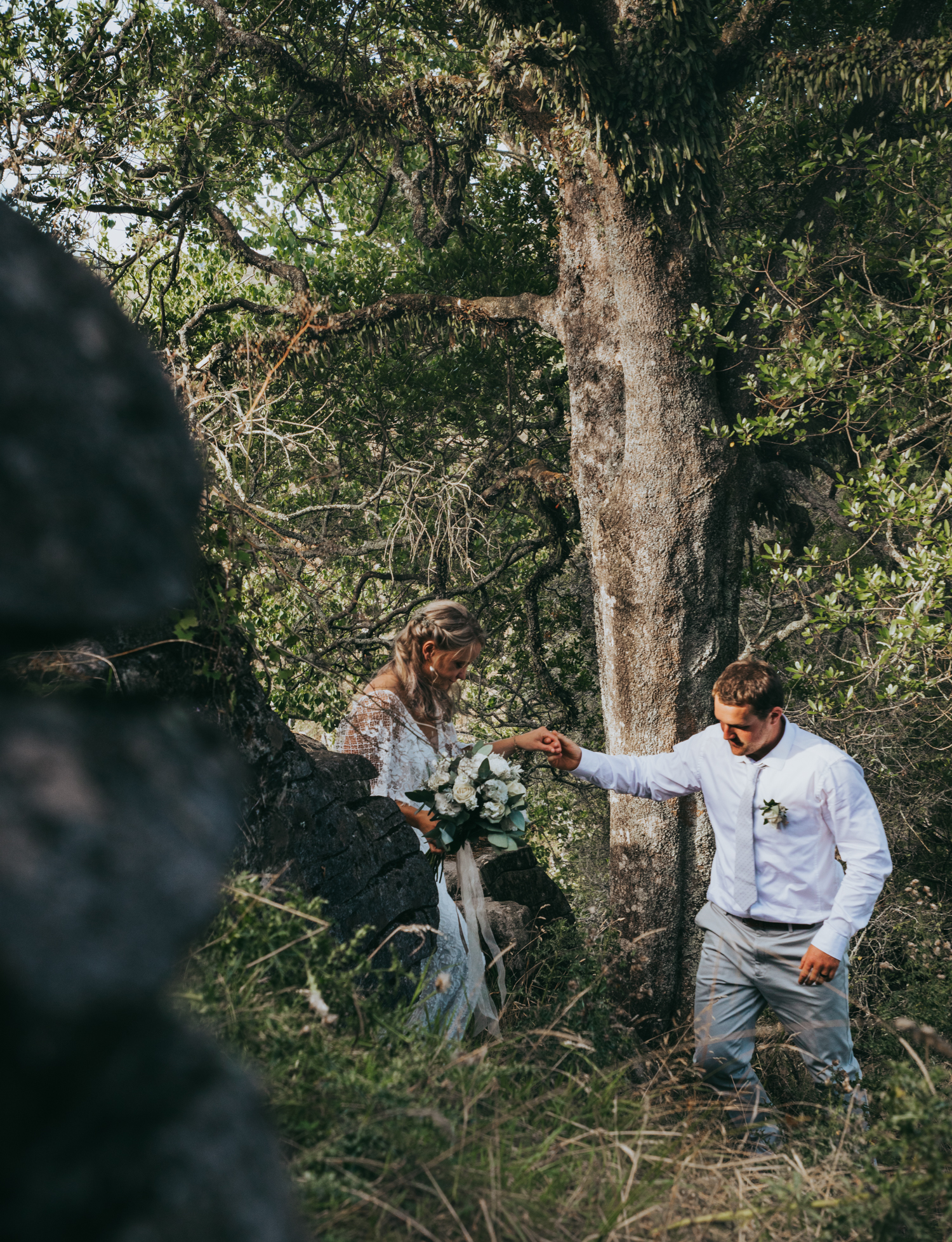 waikato-new-zealand-wedding-photographer-summer-rural-wedding-groom-helping-bride-down-the-hill.jpg