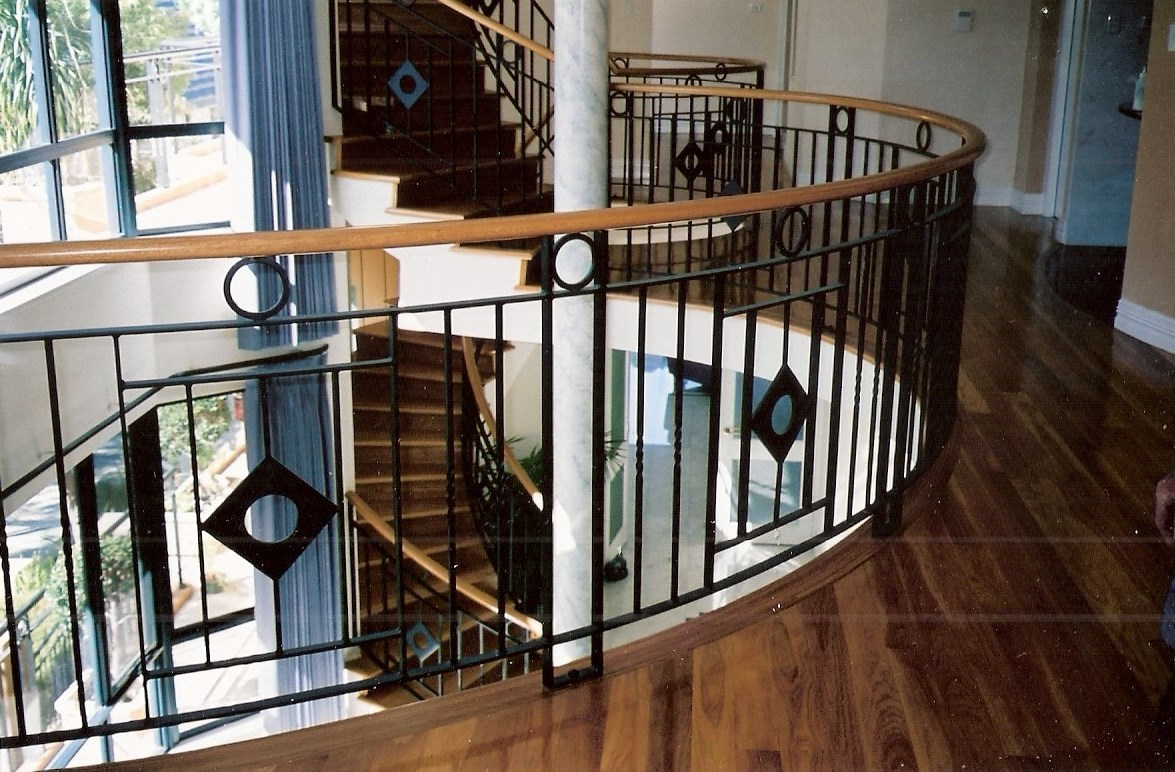 Timber staircase Perth 9 - Timber treads on cement, timber handrail on curved wrought-iron staircase.jpg