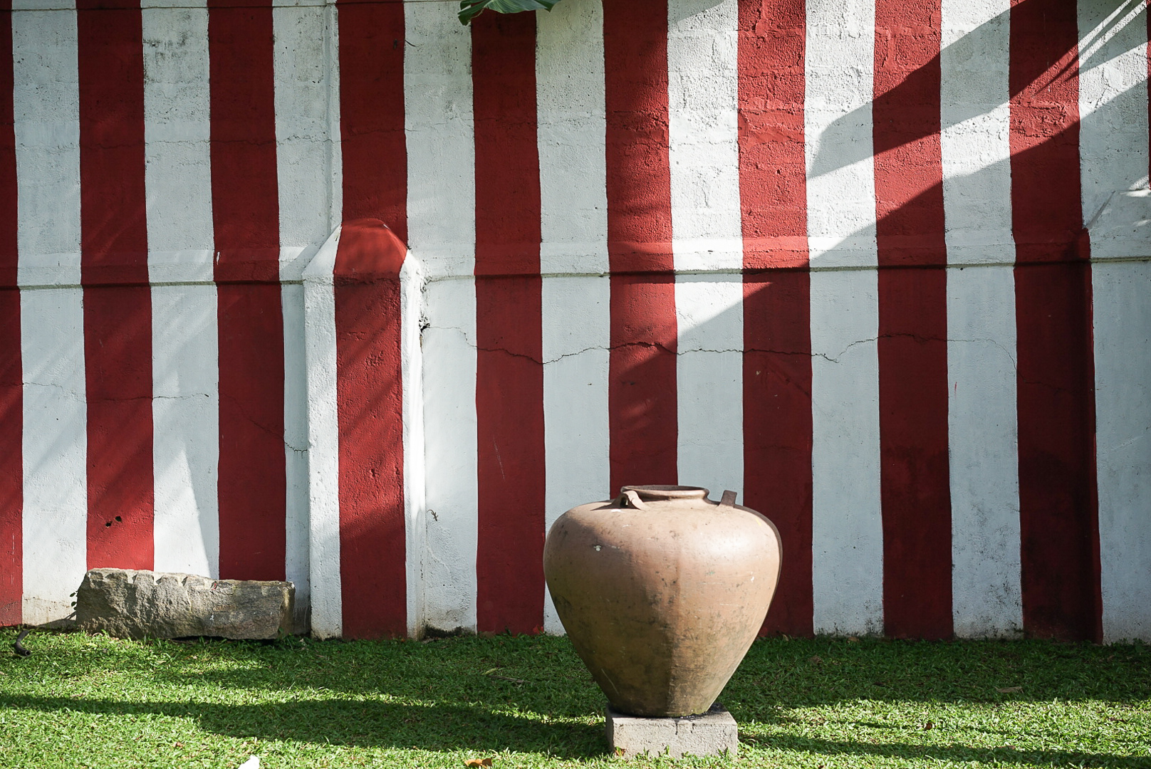 A funeral urn ornamentally placed in front of the red and white striped wall