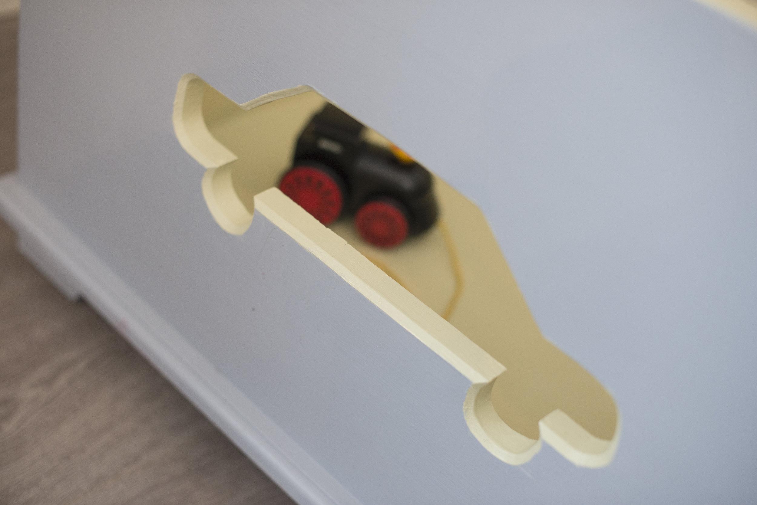 Lekekassene kan trilles på hjul og er såpass tunge at det er vanskelig å velte dem. Pluss at barna gjerne henter lekene gjennom de store utskårne mønstrene.