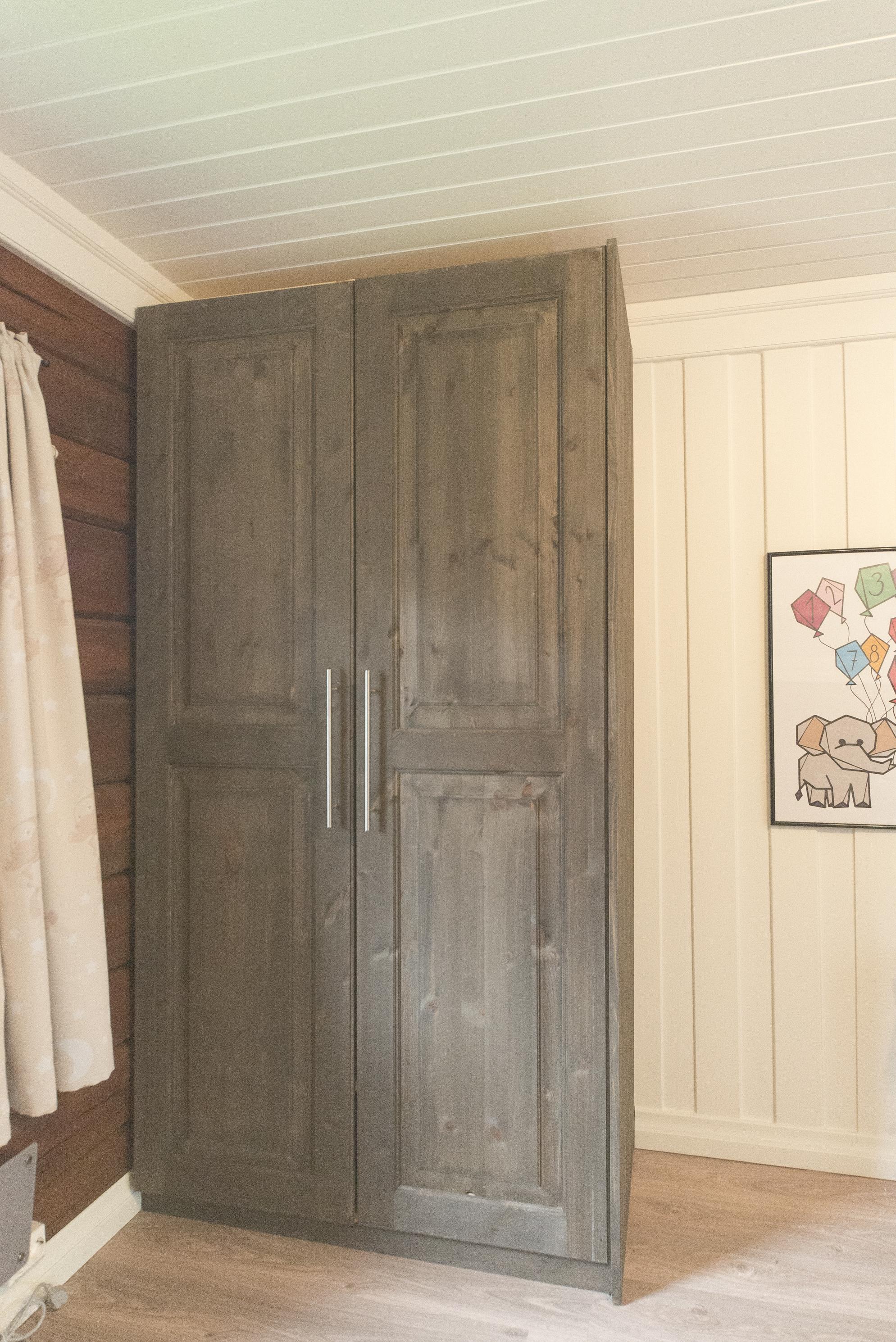Garderobeskap på barnerommet, med beis som viser trestrukturen.
