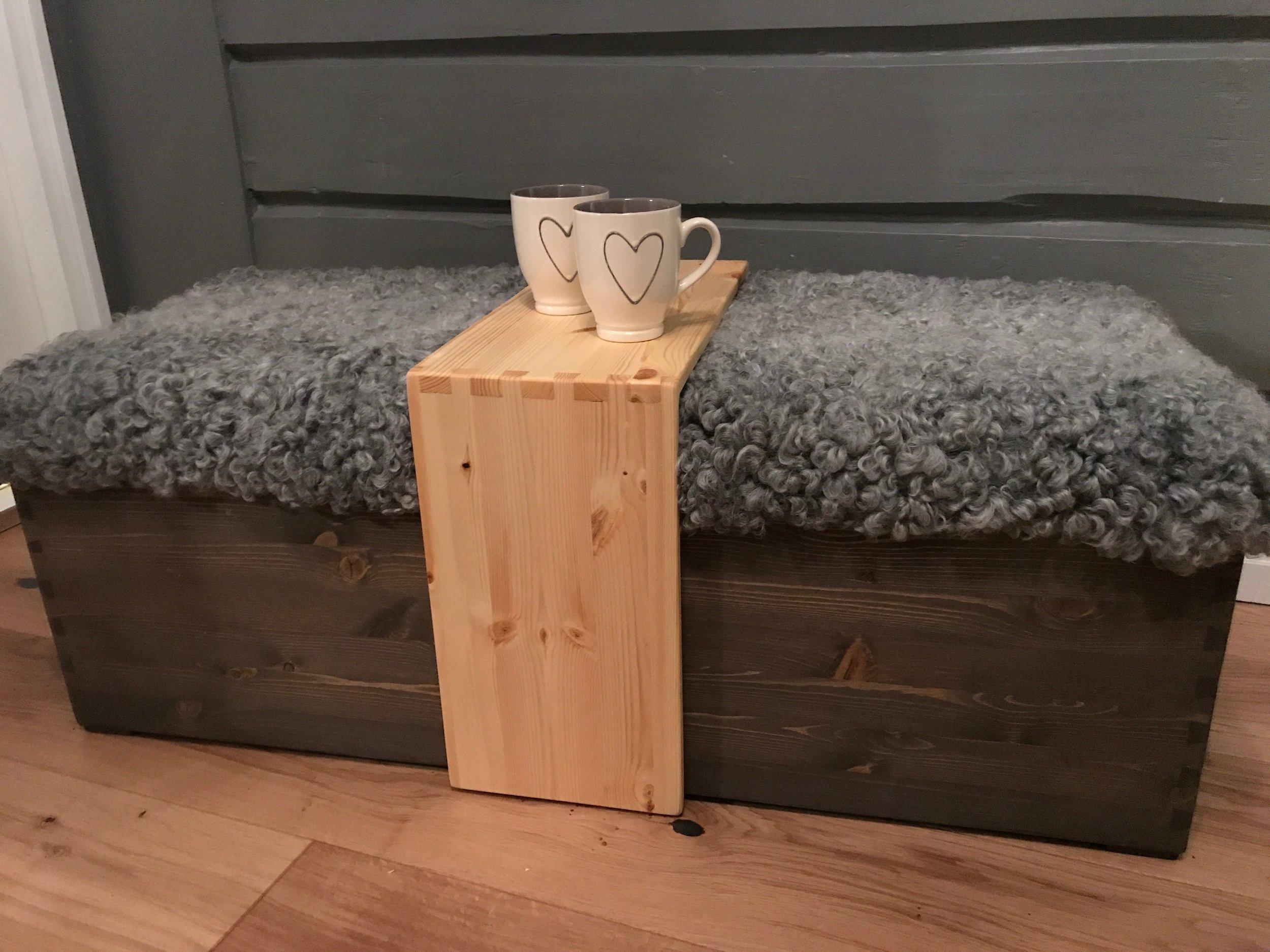 Beiset benk / kiste laget i furu. Kista er laget med en klassisk og slitesterk teknikk: håndsinkede hjørner. På toppen et lite bord som en enkelt løfter av når en skal åpne kista. Oppå kistelokket er det tapetsert inn saueskinn - en god og myk benk som en kan nyte en varm kopp te eller kaffe på.