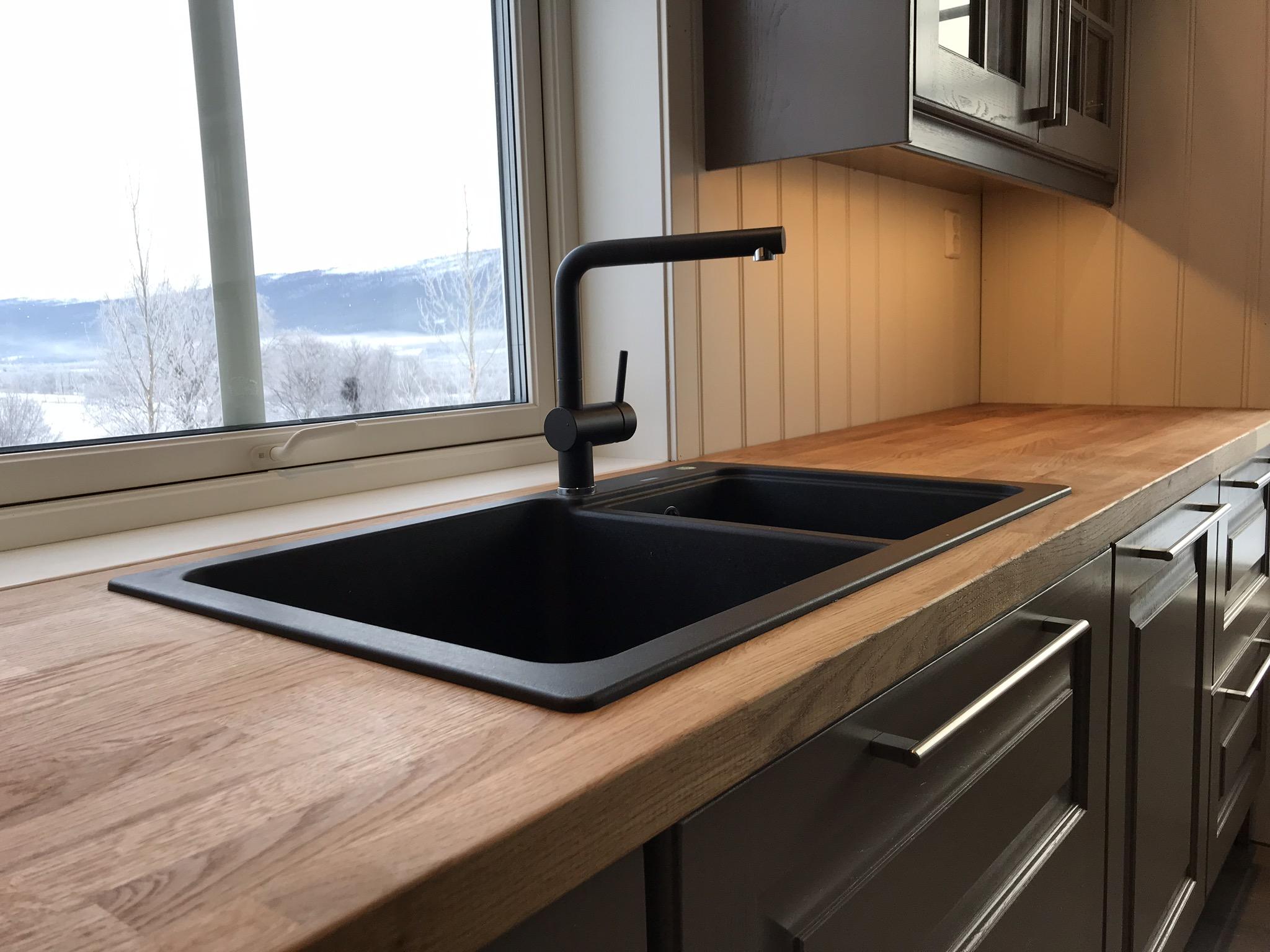 En solid benkeplate i eik som tåler mye, sammen med en svart stilren vask.