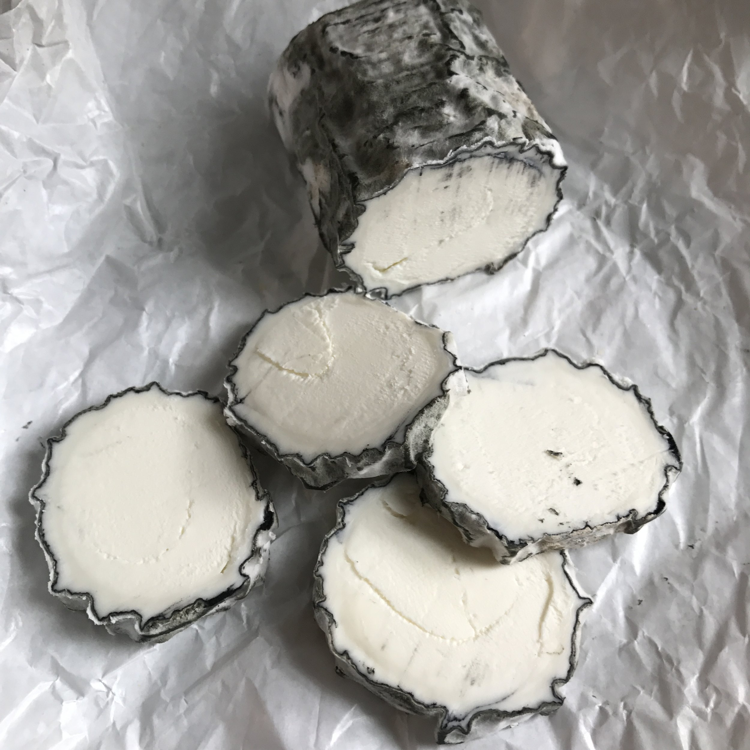 "Silver Lining - Silver Lining an elegant goat log with a mlld, slightly piquant, milky character, and a ganache-like paste. She is an aged, lactic, raw goat milk log with an ashed rind.  Silver Lining ages well for 4-7 weeks, and sometimes longer to achieve a dry or ""sec"" cheese. She is luscious anytime in her ripening process, as she becomes creamy with age. She's a classic!"