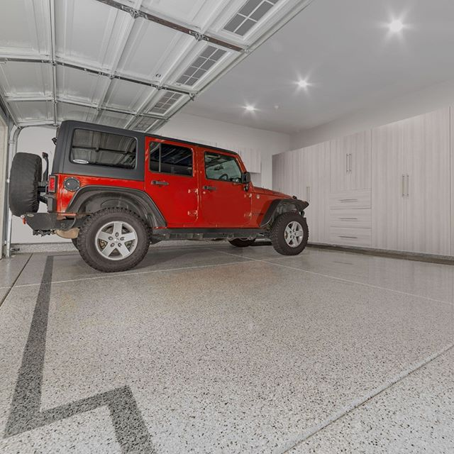This Custom Epoxy Floor Was Designed to Provide a Sleek and Clean Look but With an Eye-Catching Edge Provided By This One of a Kind Border! The Cabinets Provide a Ton of Storage and are a Perfect Compliment to Complete This Brand New Renovated Garage! #EpoxyFlooring #CustomEpoxy #EpoxyFloor #Garage #CustomGarage