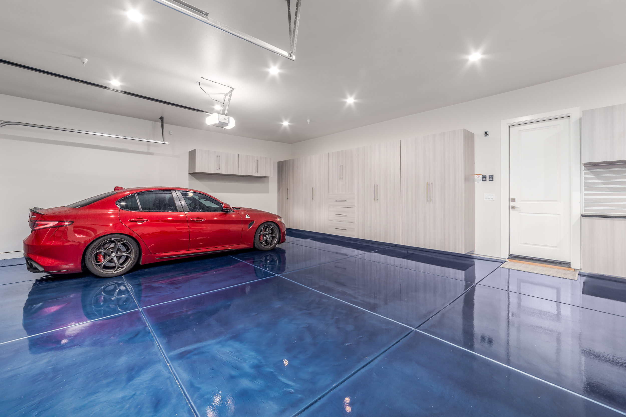 "Custom Blue Metallic Epoxy Floor with Cabinets in Folsom   This customer wanted a garage that would highlight his car collection as well as something that would dazzle his neighbors, friends, and family. He chose a custom ocean blue metallic floor along with our ""looks like a tree"" cabinets. Each metallic floor is completely one of a kind unique and this one was no different!"