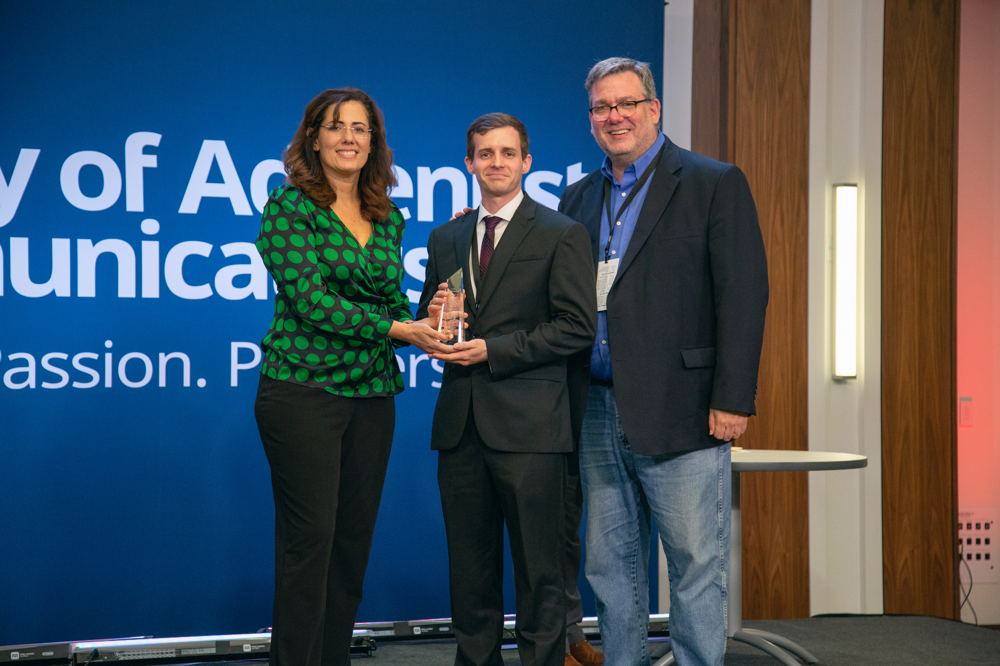 "Shane Hochstetler (center) accepts the ""Cutting Edge Award"" for his work on the Gulf States Camp Meeting Campaign, ""Forgiven to Forgive."" The award is presented by Libna Stevens (left), president of SAC, and Daniel Weber (right), executive director of SAC. Photo: Pieter Damsteegt"