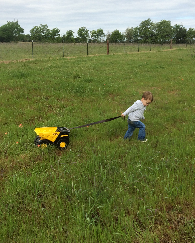 Dr. Anderson's grandson enjoying nature and Tonka trucks.